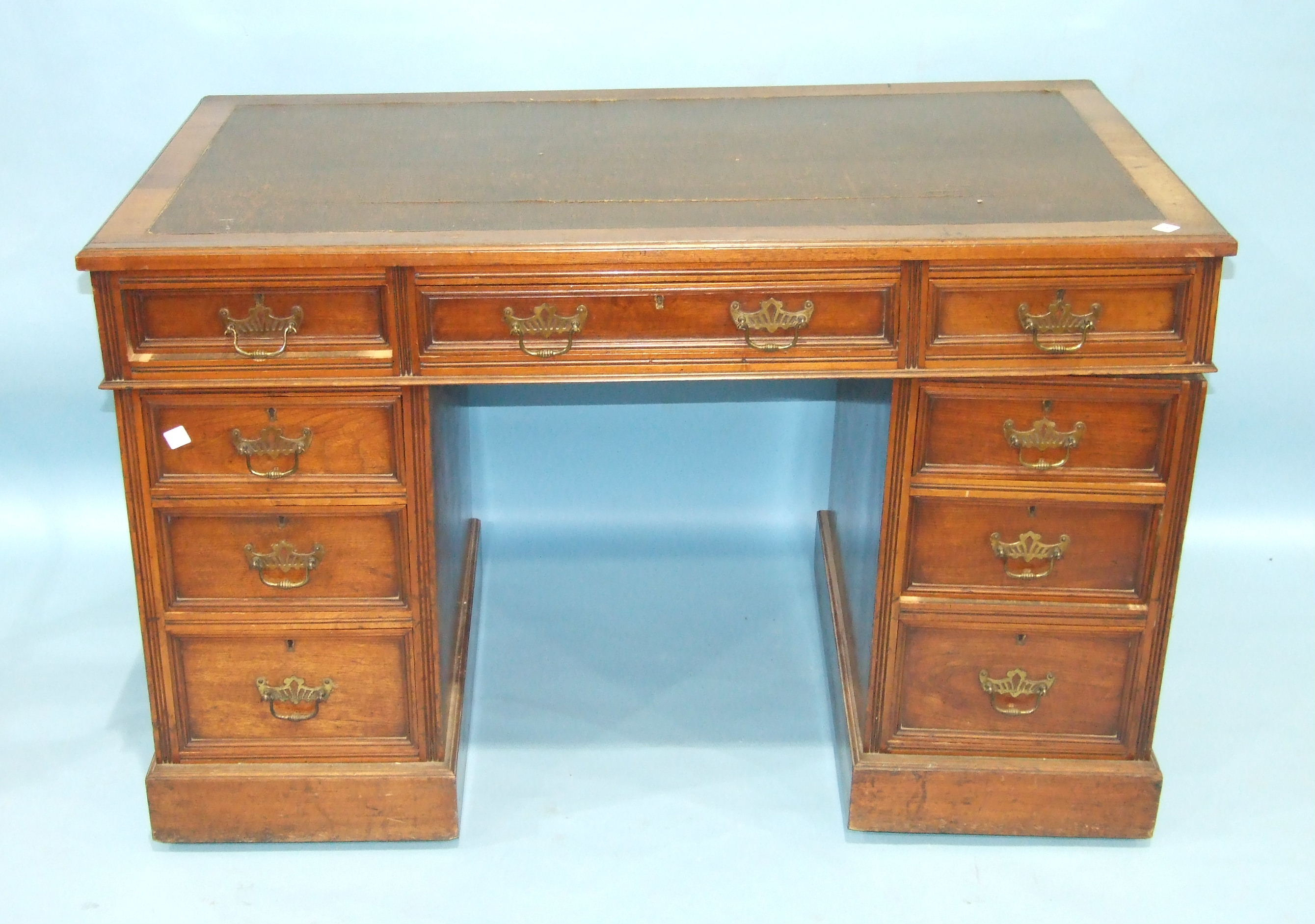 Lot 96 - A late-Victorian walnut kneehole writing desk, the rectangular top with inset writing surface