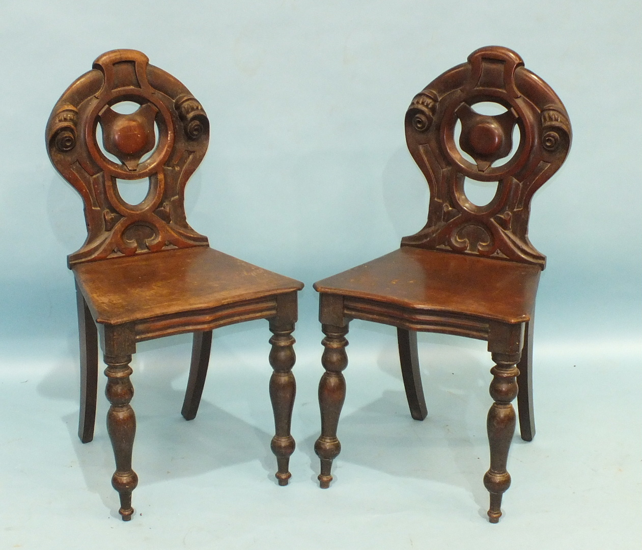 Lot 64 - A pair of mahogany hall chairs with pierced backs and shaped solid seats, on turned front legs, (