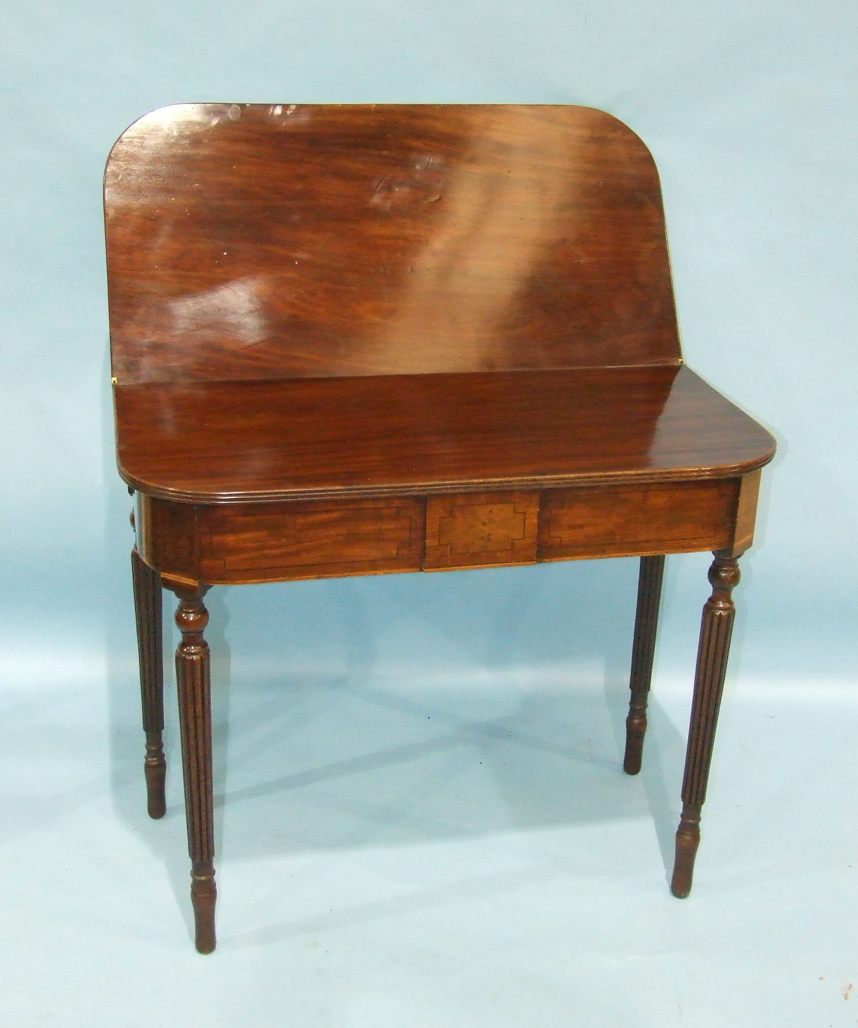 Lot 88 - A late-Georgian mahogany tea table, the rectangular reeded fold-over top with rounded corners, on