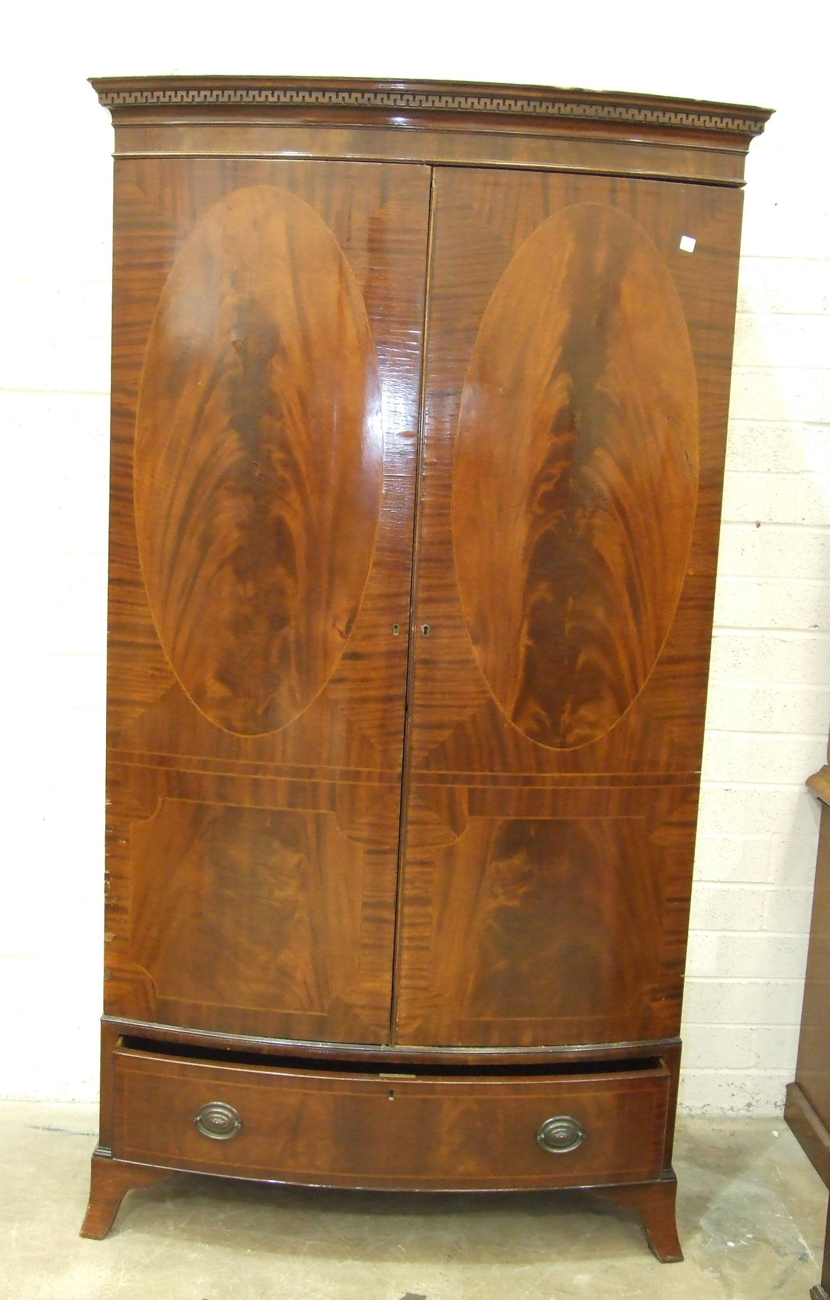 Lot 65 - A Georgian-style mahogany bow-fronted two-door wardrobe, with dentil cornice and base drawer,