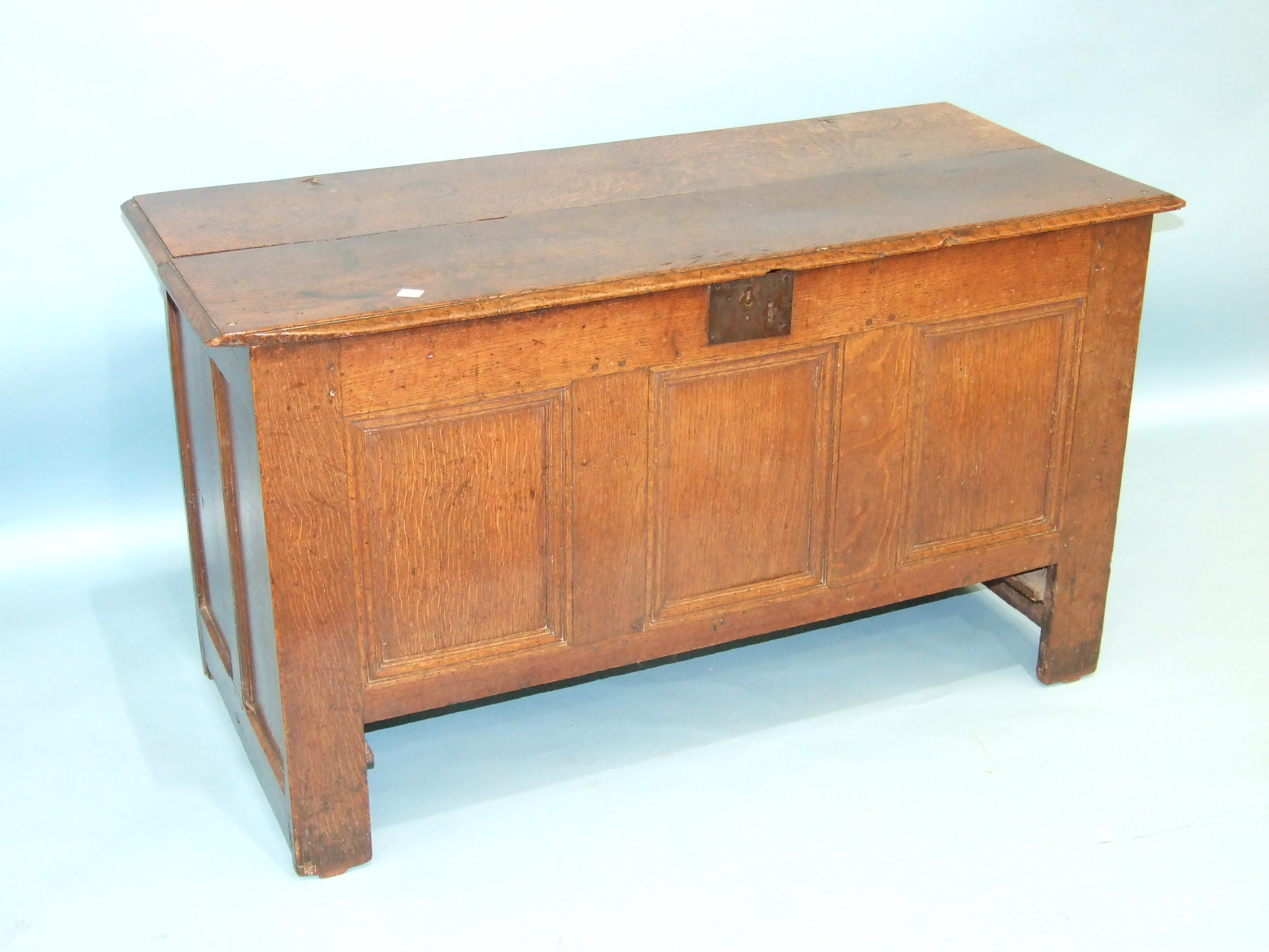 Lot 76 - An 18th century oak panelled coffer with hinged lid, (repaired), drawer beneath lacking, 121cm