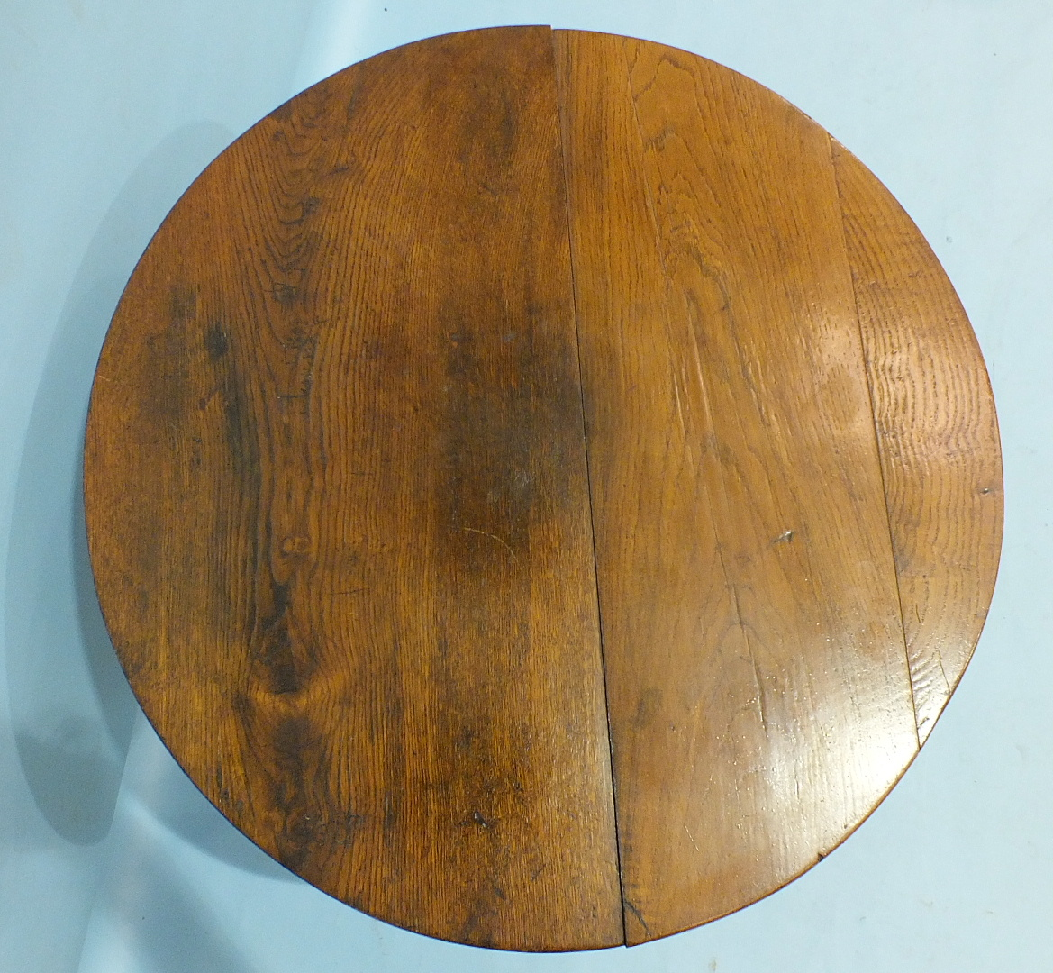 Lot 113 - An antique oak tilt-top occasional table on turned column and tripod support, 75cm diameter.
