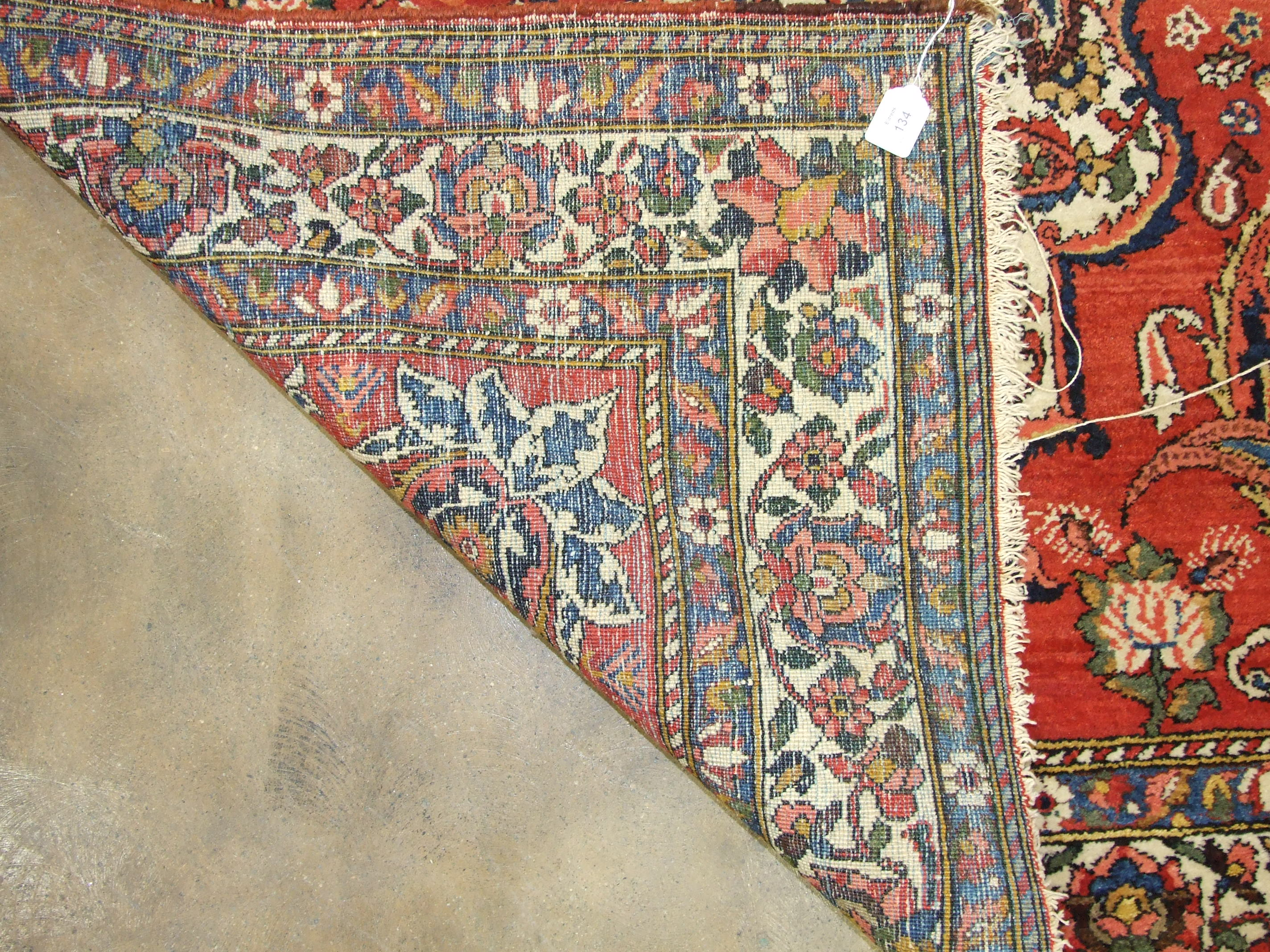 Lot 134 - An Oriental rug with central medallion, on red ground and foliate borders, 224 x 136cm.