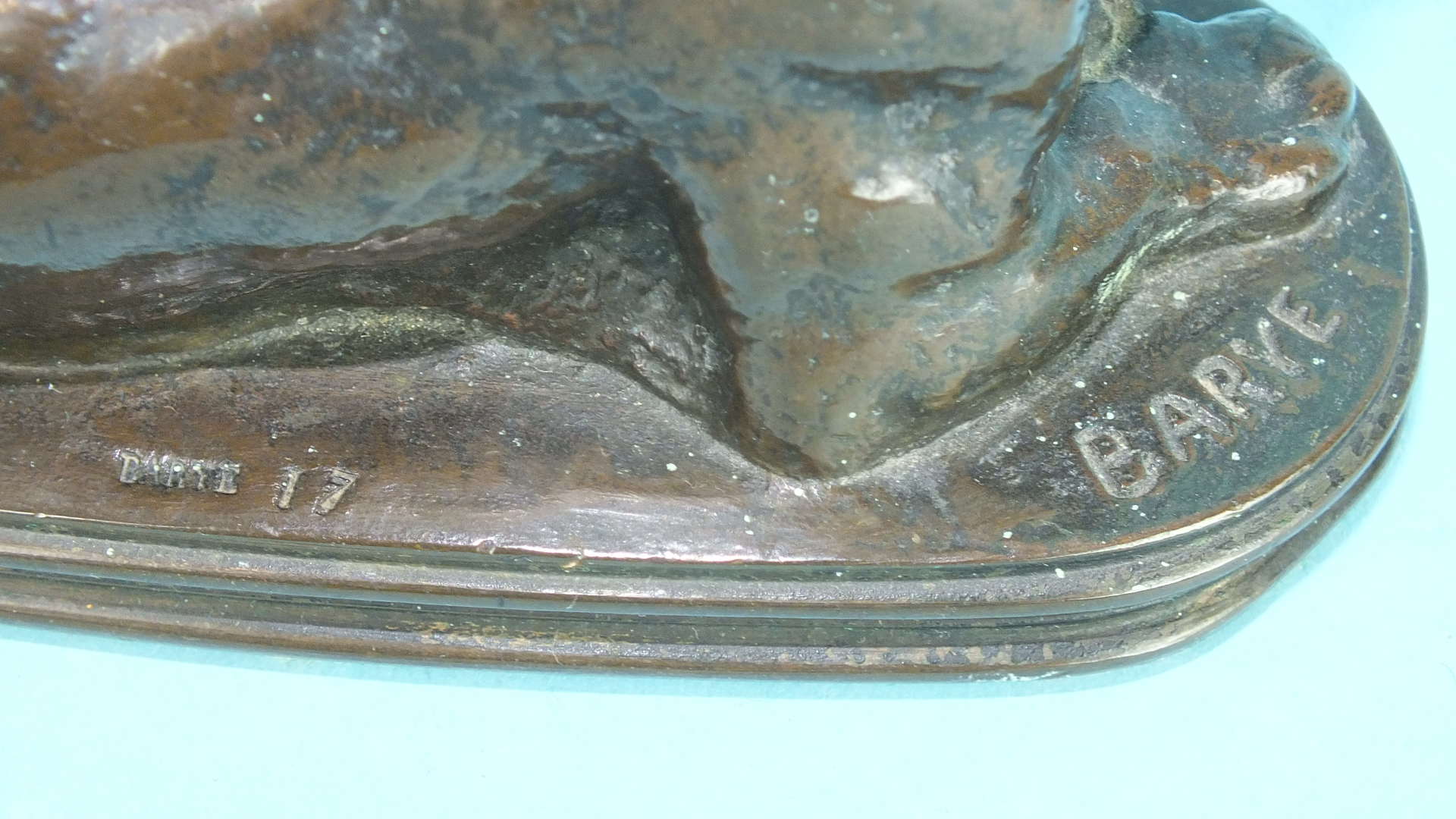 Lot 161 - After Antoine-Louis Barye, a bronze study of a lioness lying down, on shallow reeded-edge plinth,