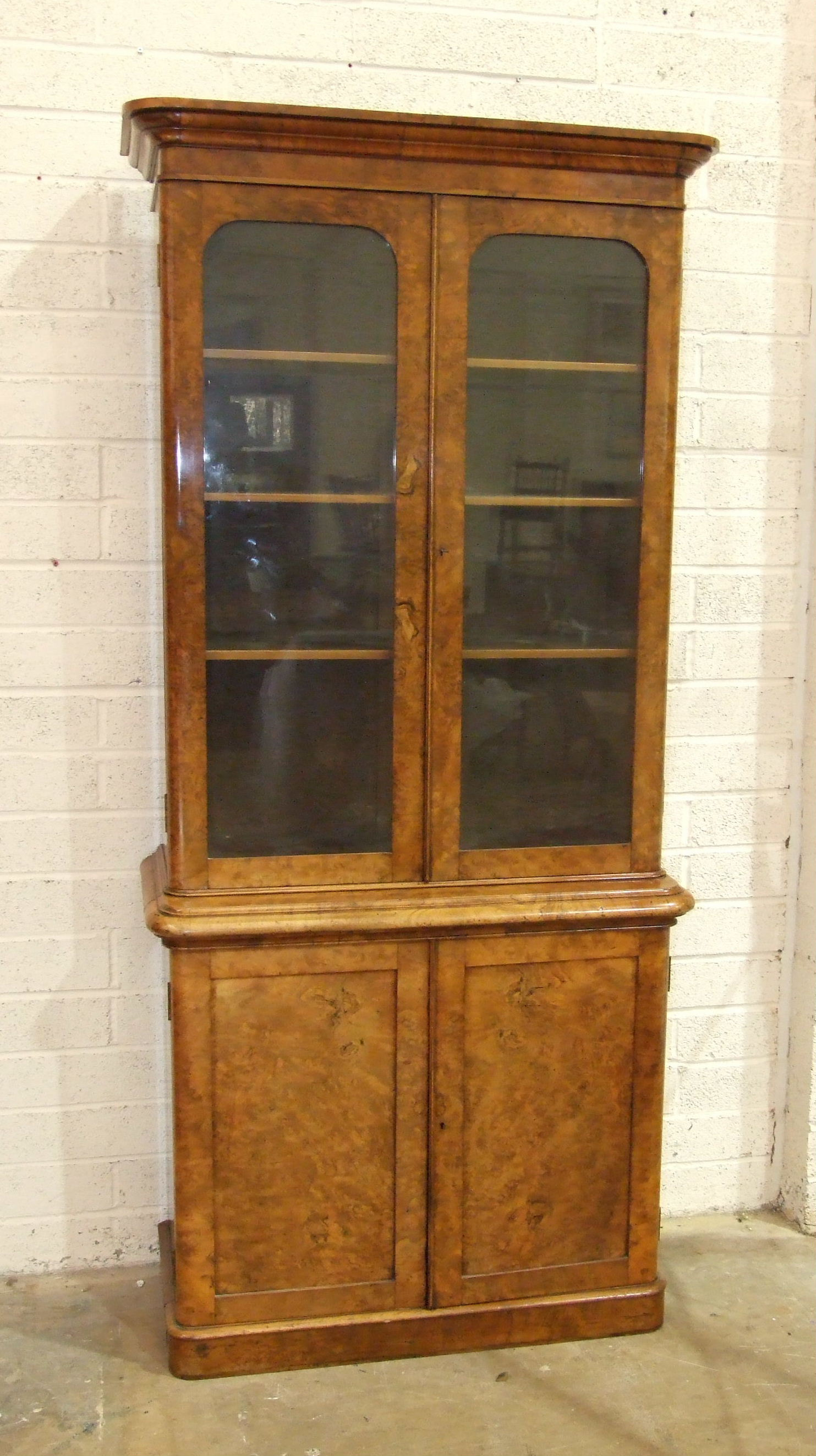 Lot 68 - A Victorian burr walnut bookcase, the moulded cornice above a pair of plain glazed doors and a