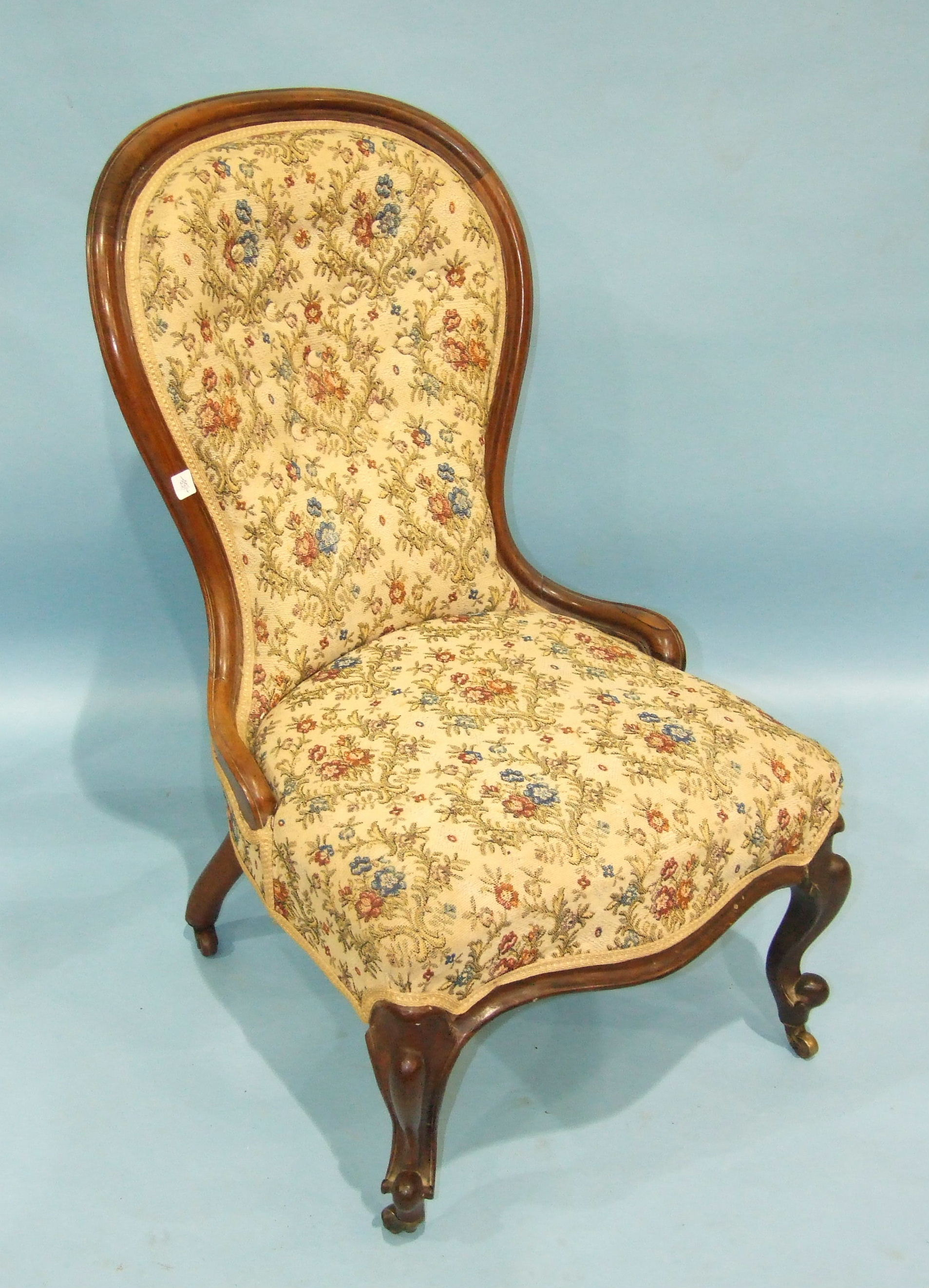Lot 72 - A Victorian rosewood spoon-back nursing chair with serpentine seat and button back, on carved