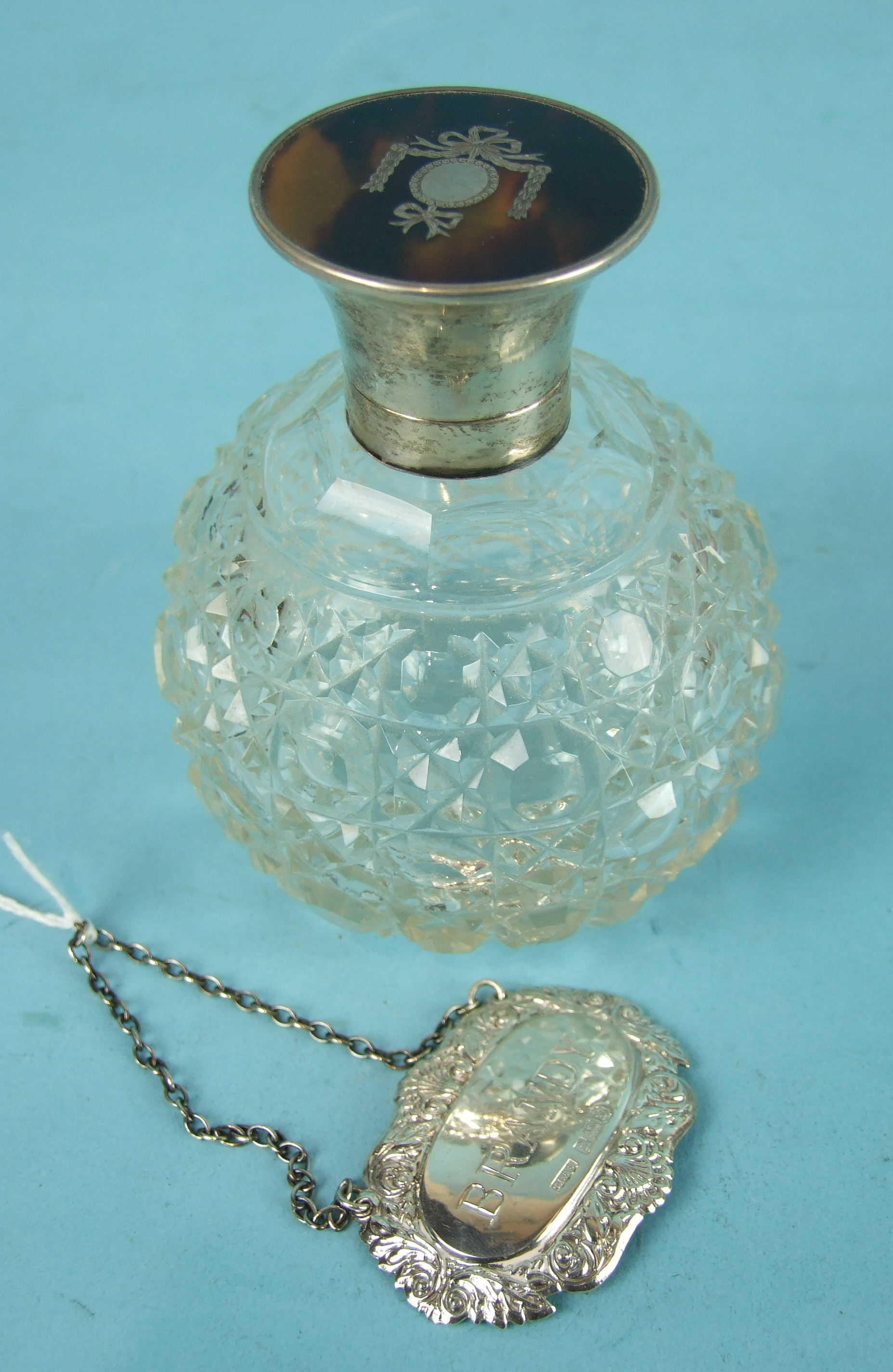 Lot 517 - An early-20th century cut-glass globe shape scent bottle with silver and tortoiseshell lid, 11.5cm