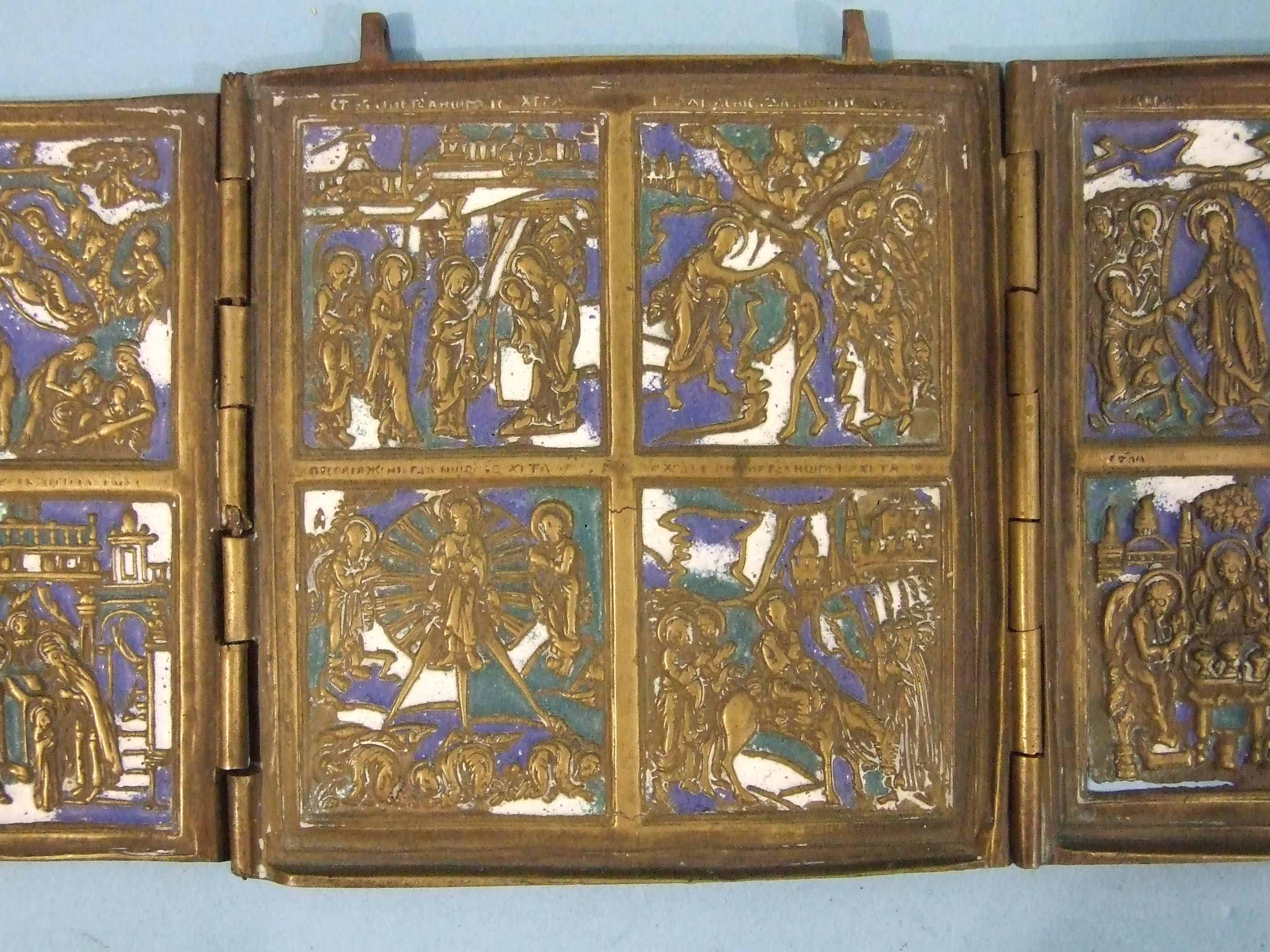 Lot 148 - An antique brass and enamelled triptych icon, each of the three hinged panels divided into four