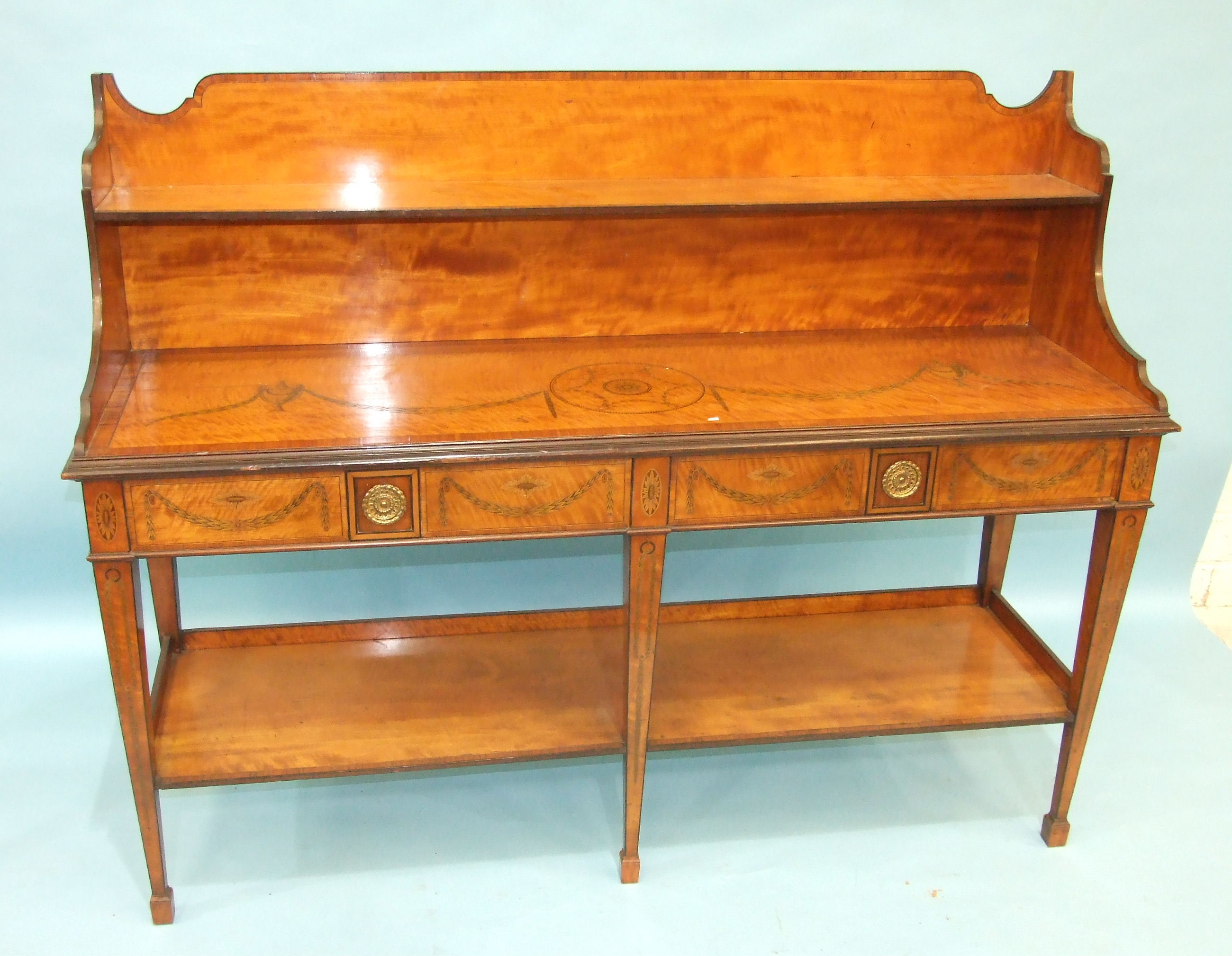 Lot 85 - An inlaid and cross-banded satinwood serving table in the Adam taste, the low shelved back above a