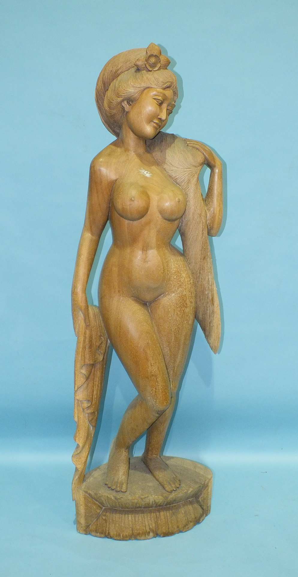 Lot 178 - A Thai carved wood figure of a naked young woman with long flowing hair, standing on a plinth, 154cm