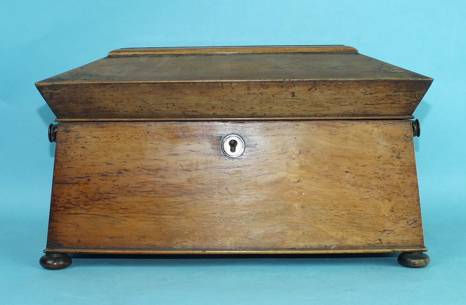 Lot 160 - An early-19th century rosewood sarcophagus-shaped three-division tea caddy on bun feet, with