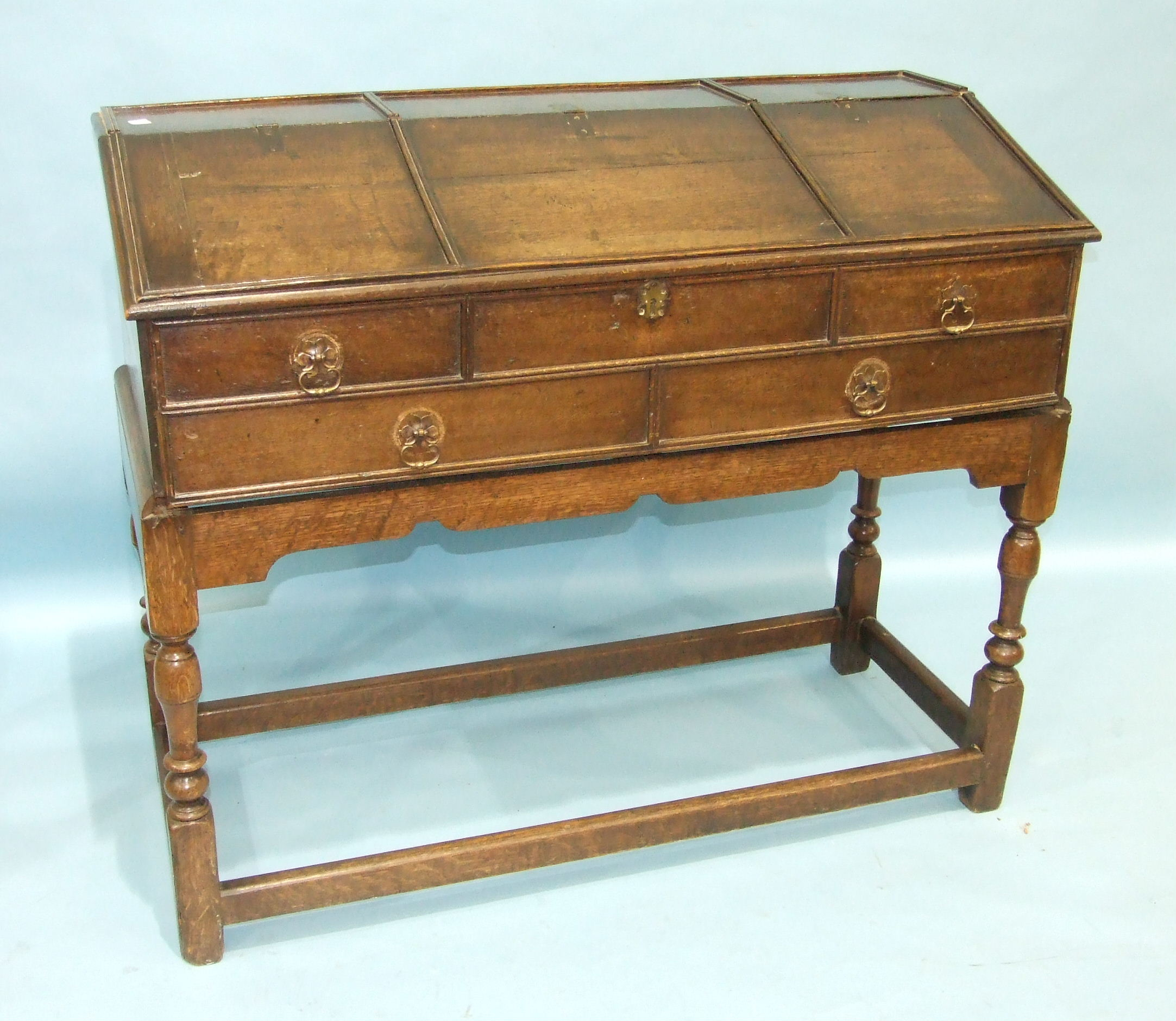 Lot 94 - An antique oak fall-front clerk's desk enclosing a fitted interior, on turned legs joined by