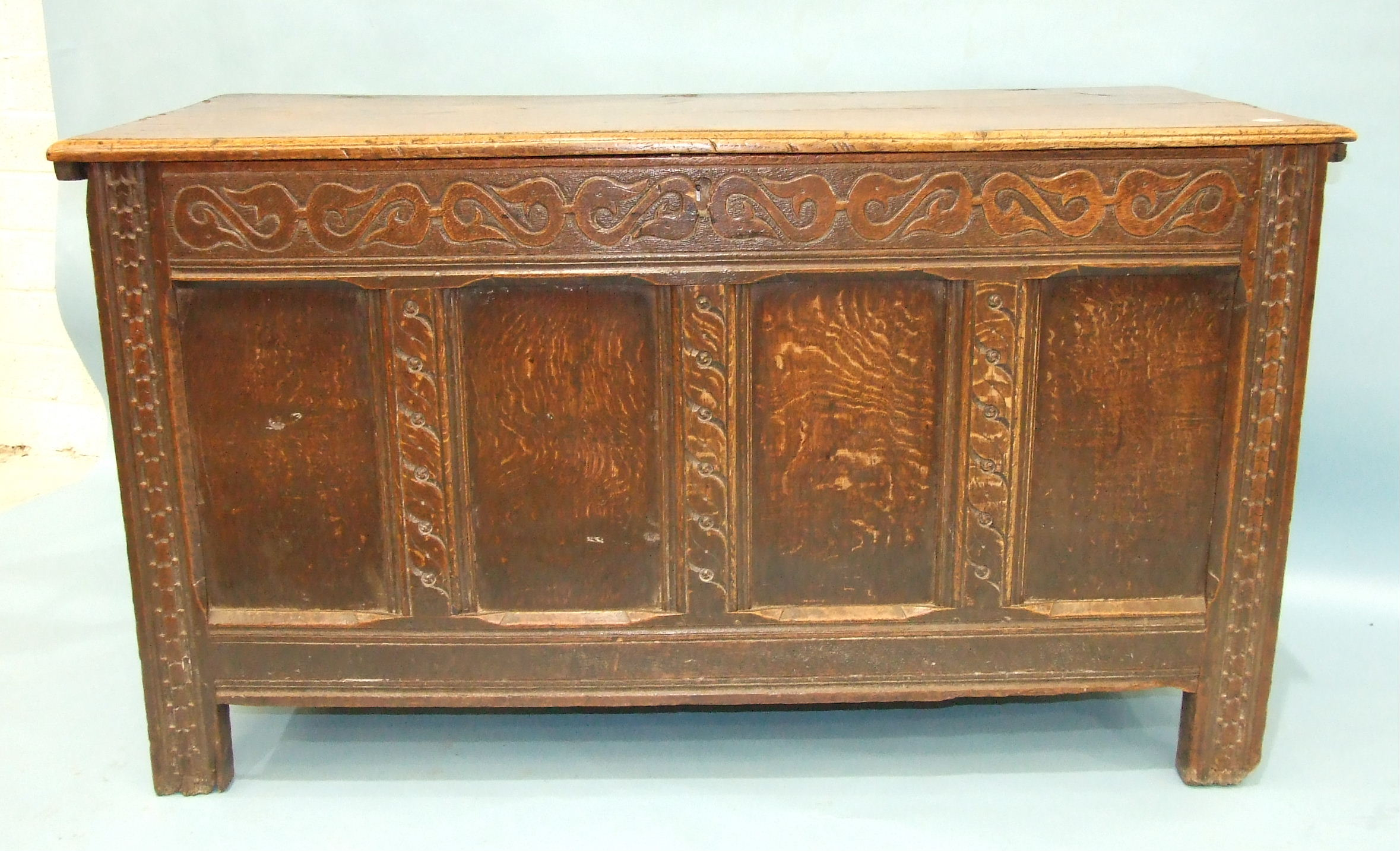 Lot 77 - An antique oak coffer with carved panelled front and sides, stiles extended to form feet, 131cm
