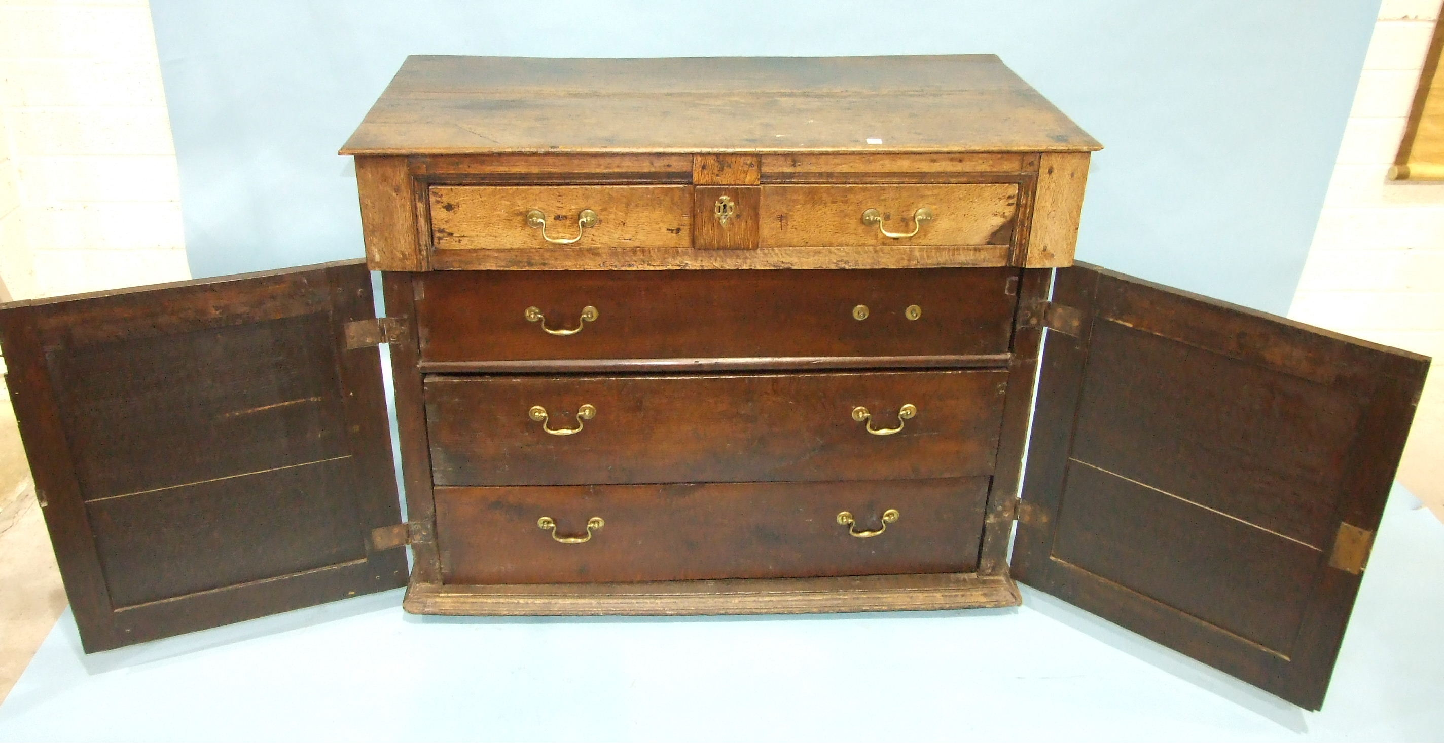 Lot 95 - An antique oak chest having a frieze drawer above a pair of panelled doors, enclosing three