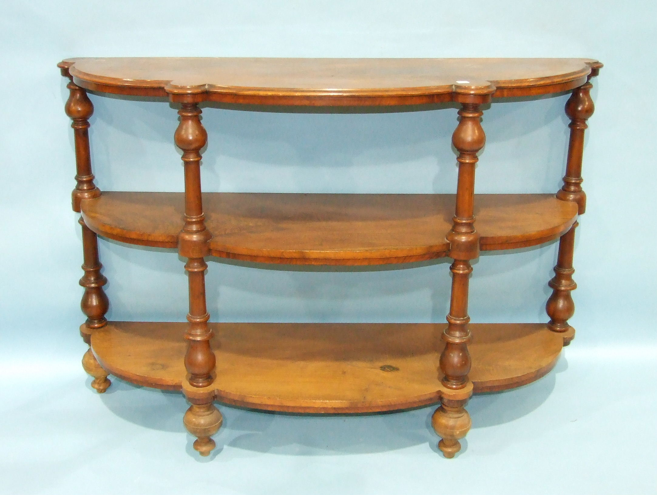 Lot 86 - A Victorian three-tier whatnot of shaped bowed outline, each tier separated by turned columns, 136cm