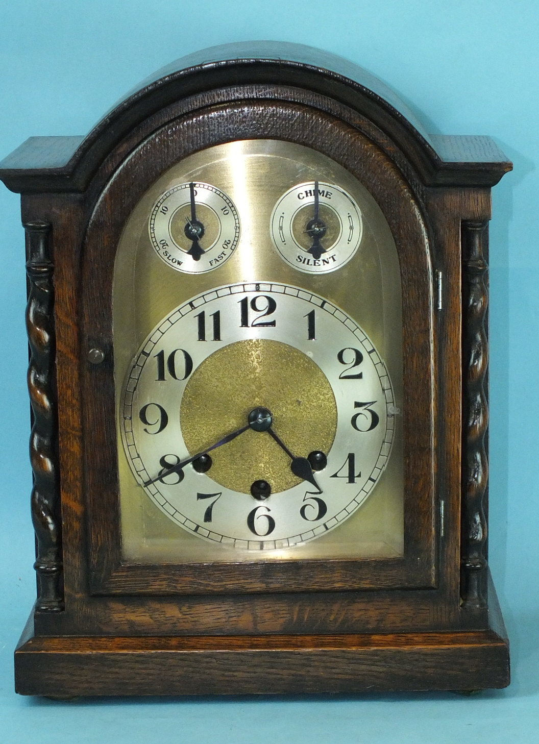 Lot 127 - A 20th century oak mantel clock, the dial with silvered chapter ring, chime/silent and slow/fast