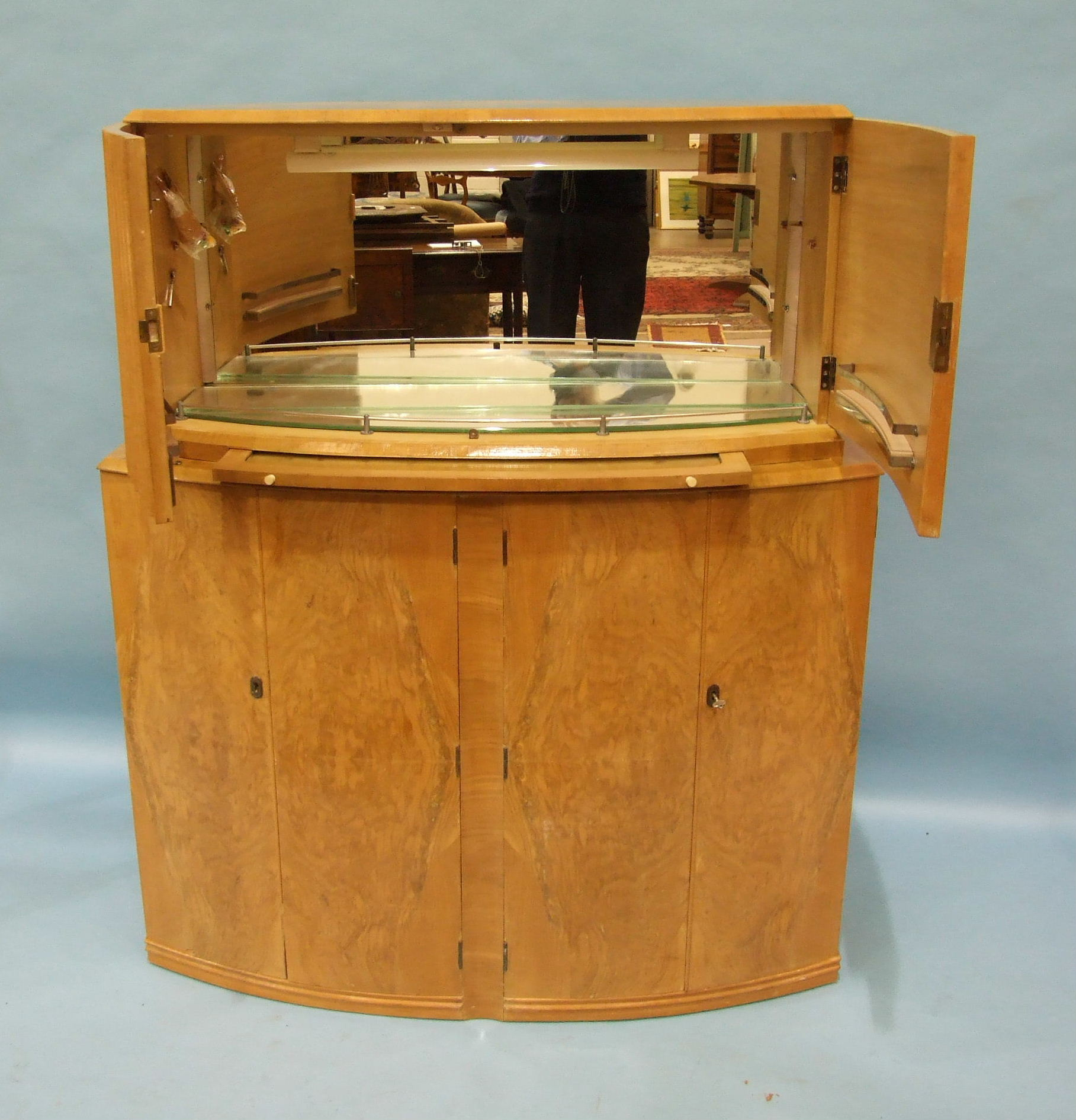 Lot 67 - An Art Deco satin birch cocktail cabinet, having a pair of fluted hinged doors enclosing mirrored