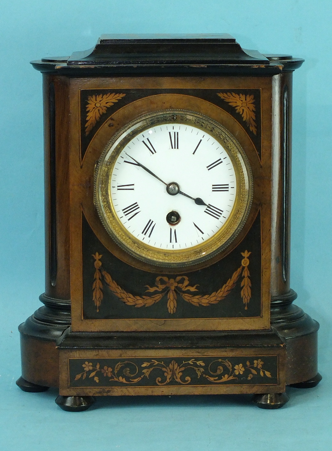 Lot 128 - A 19th century walnut and mahogany mantel clock with circular enamelled dial and drum movement, 27cm