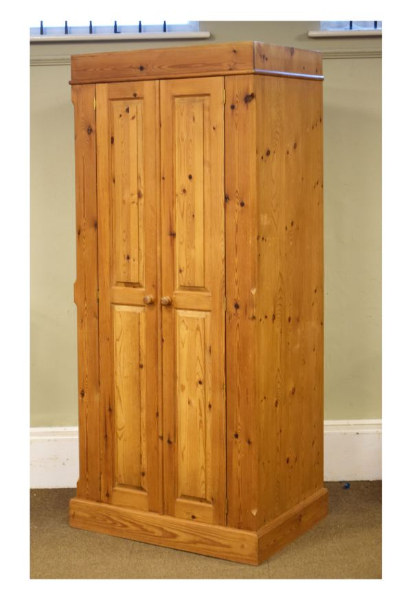 Lot 20 - 20th Century yellow pine wardrobe having a pair of twin fielded panelled doors enclosing a hanging