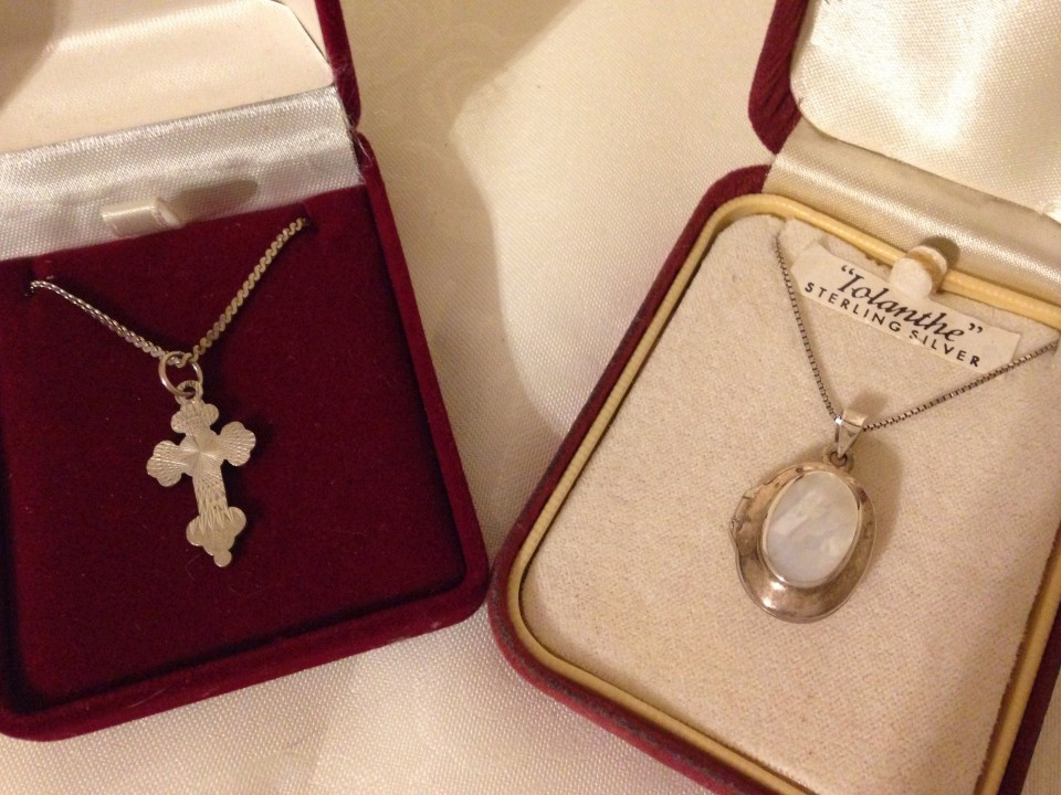 Lot 1057 - An oval silver locket set with mother of pearl, together with a silver cross - both on silver chains