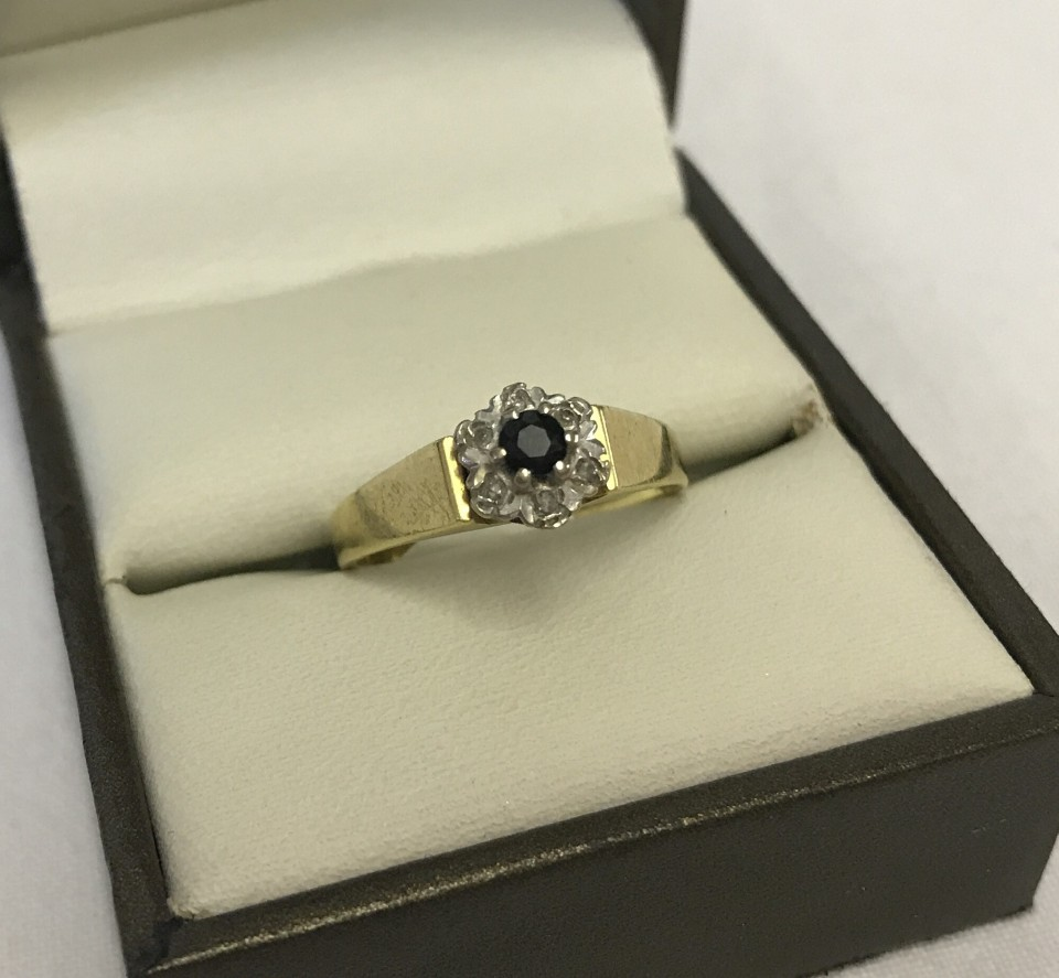 Lot 1037 - A hallmarked 18ct gold sapphire and diamond cluster ring.