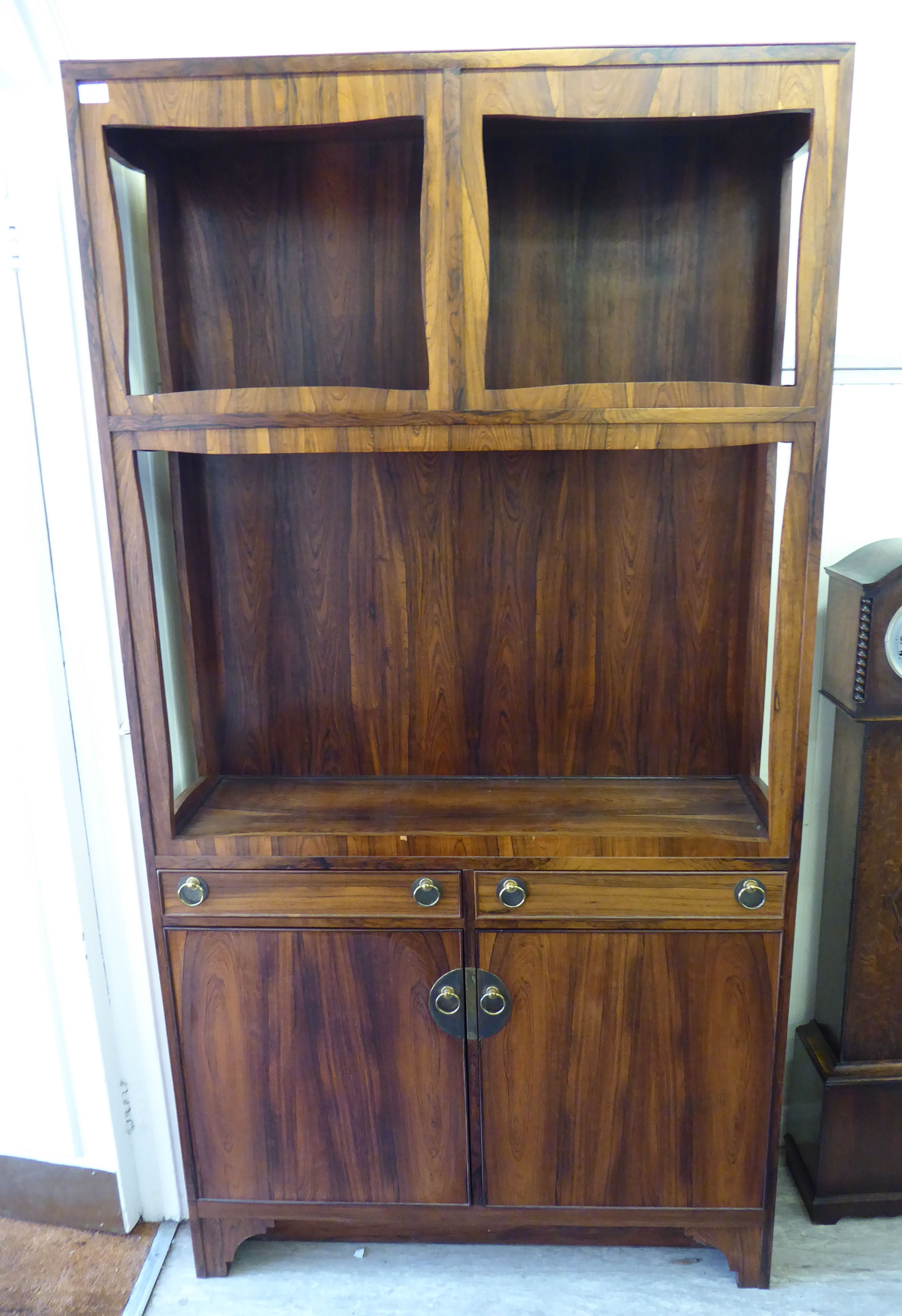 Lot 7 - An early 1970s bespoke rosewood cabinet, the superstructure comprising three open display shelves,