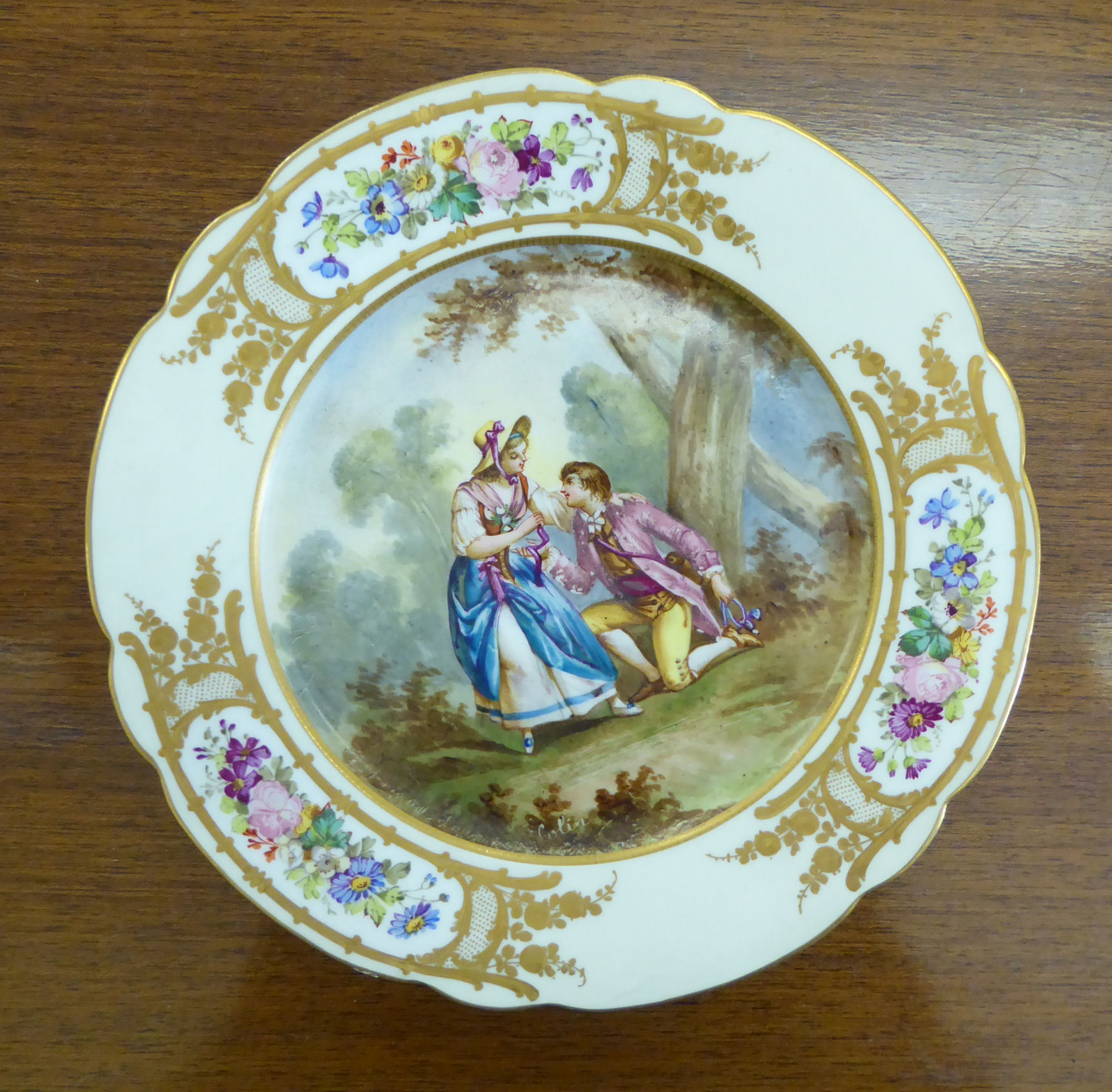 Lot 3 - A mid 19thC Sevres porcelain wavy edge plate, featuring a romantic scene,