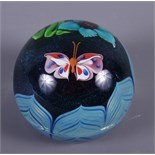 """A glass paperweight decorated central butterfly, flowers and leaves, base engraved """"EL53M 1978"""