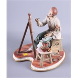 A Continental porcelain figure of an artist seated at his easel