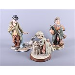 Three Capodimonte figures, a man with a dog, a tramp and a grandmother putting children to bed