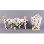 A mid 20th century Continental porcelain table centre, basket with cherub supports and floral relief