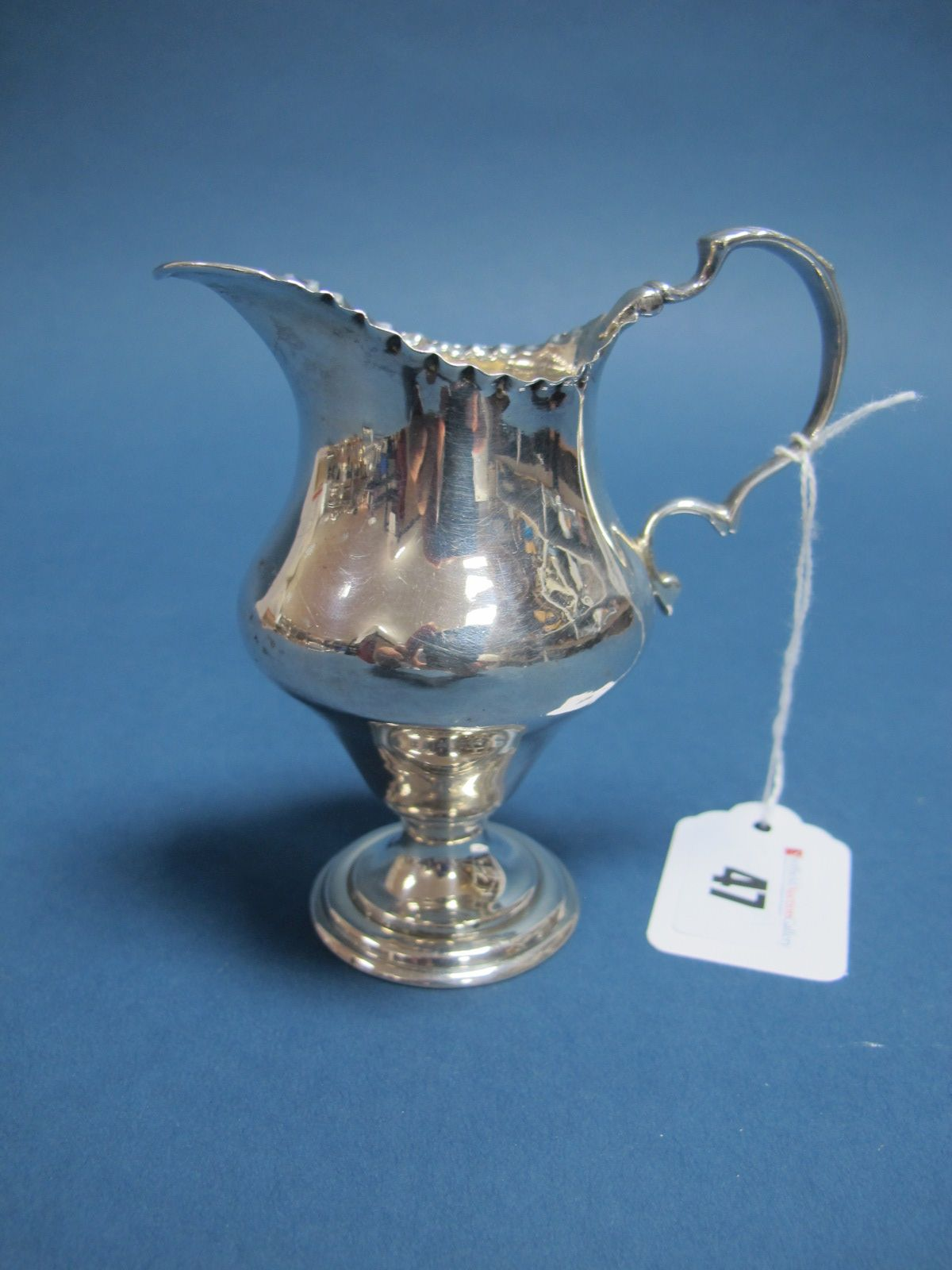 Lot 47 - A Hallmarked Silver Jug, (marks rubbed) Chester, with wavy edge and leaf capped scroll handle, on