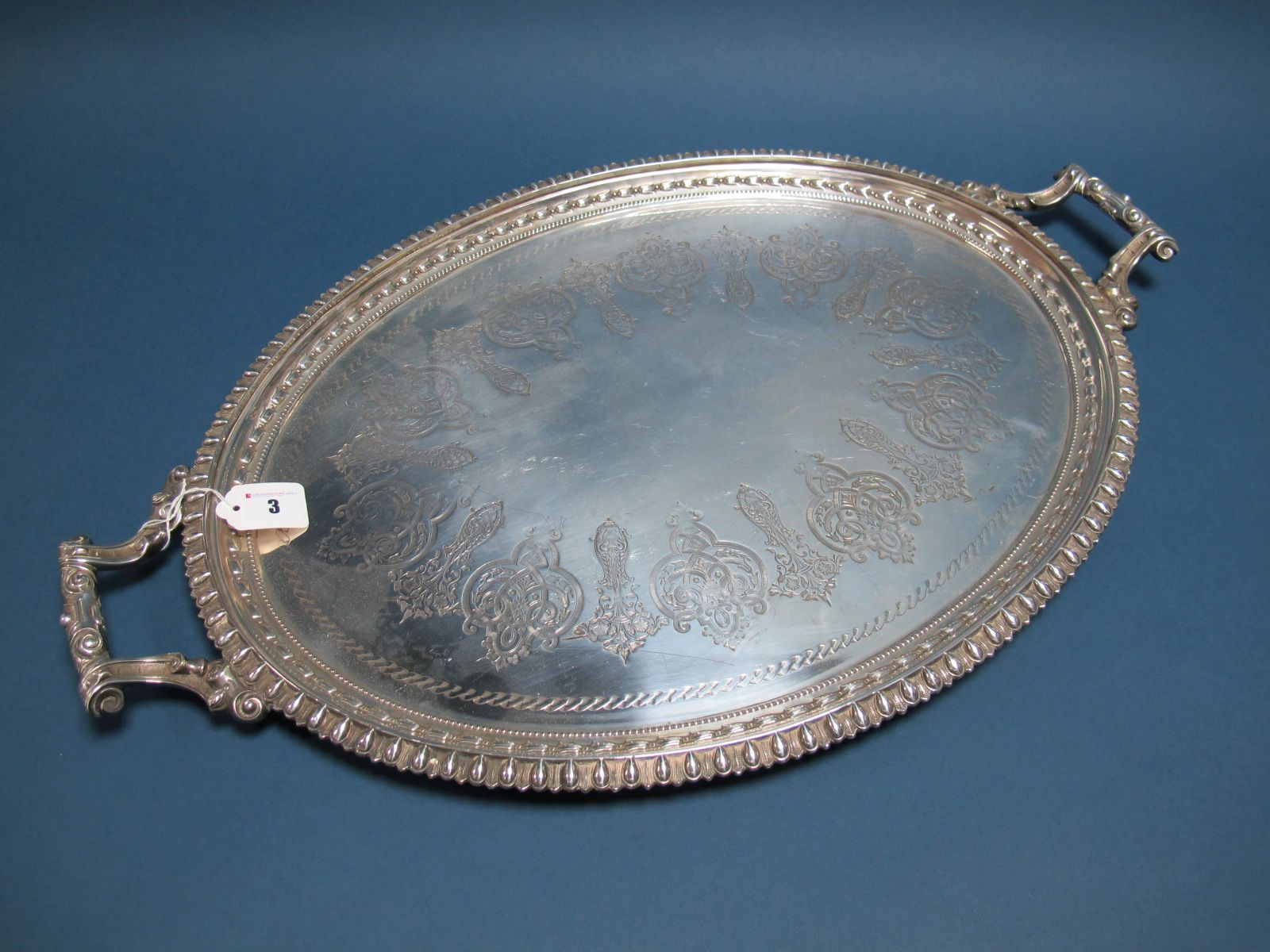 Lot 3 - A Large Plated Oval Twin Handled Tray, detailed in relief with decorative border, between angular