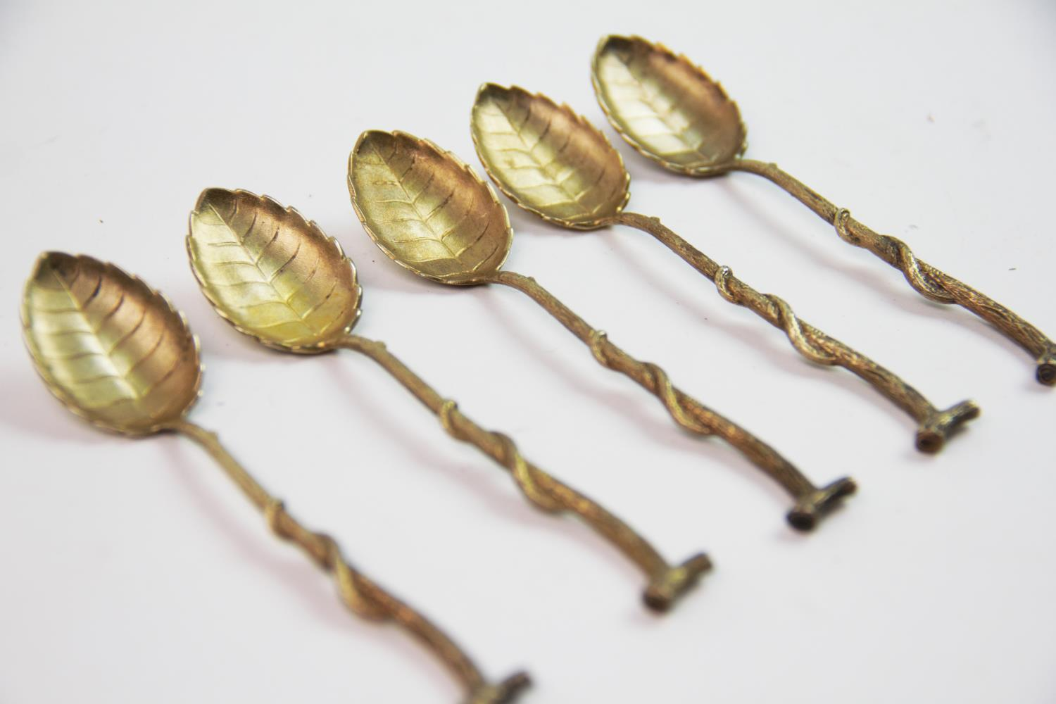 Lot 21 - A set of eleven continental silver gilt teaspoons, the bowls designed as leaves, the handles of twig