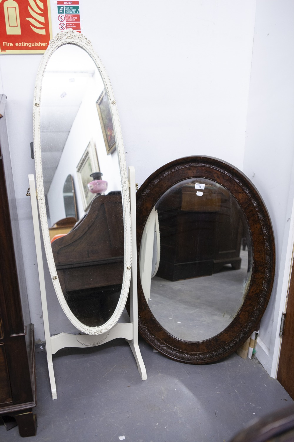 Lot 46 - A LARGE OVAL WALL MIRROR WITH BEVELLED EDGE IN STAINED WOOD FRAME AND A CREAM AND GILT OVAL CHEVAL