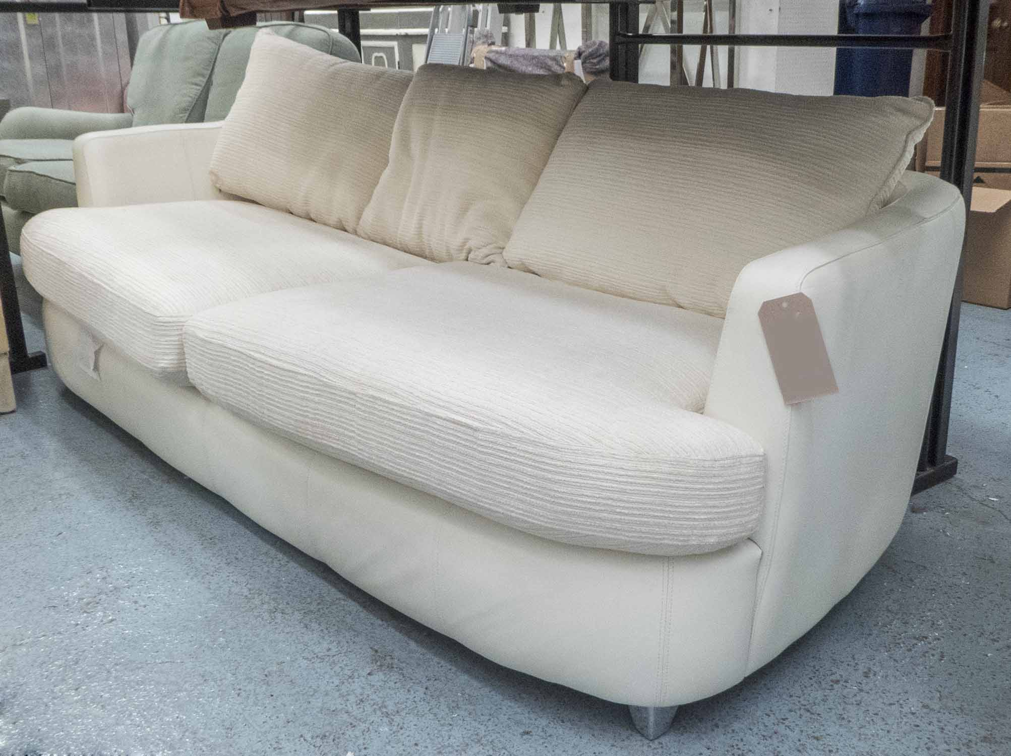 Lot 8 - SOFA, large two seater, in cream leather and cream fabric on metal supports, 231 cm long.