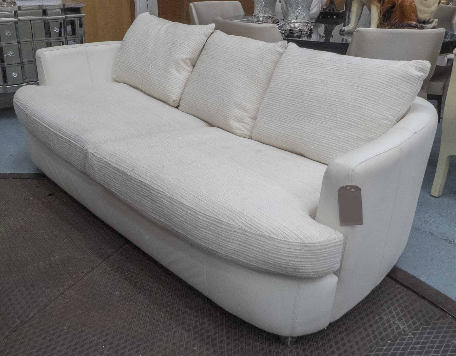 Lot 7 - SOFA, two large seater, in cream leather and cream fabric, on metal supports, 231cm long.