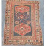 A Caucasian rug, of geometric design with two central medallions, and centre star gul enclosed