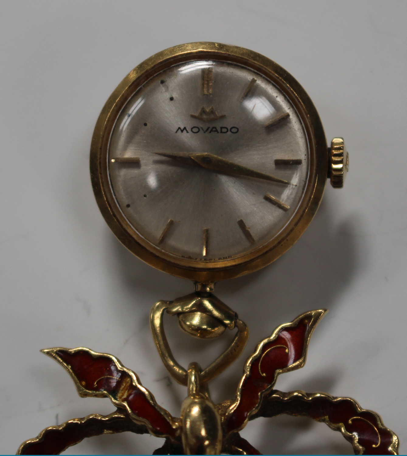 Lot 999 - A Movado 18ct gold and red enamelled pendant watch with a signed jewelled movement, the signed