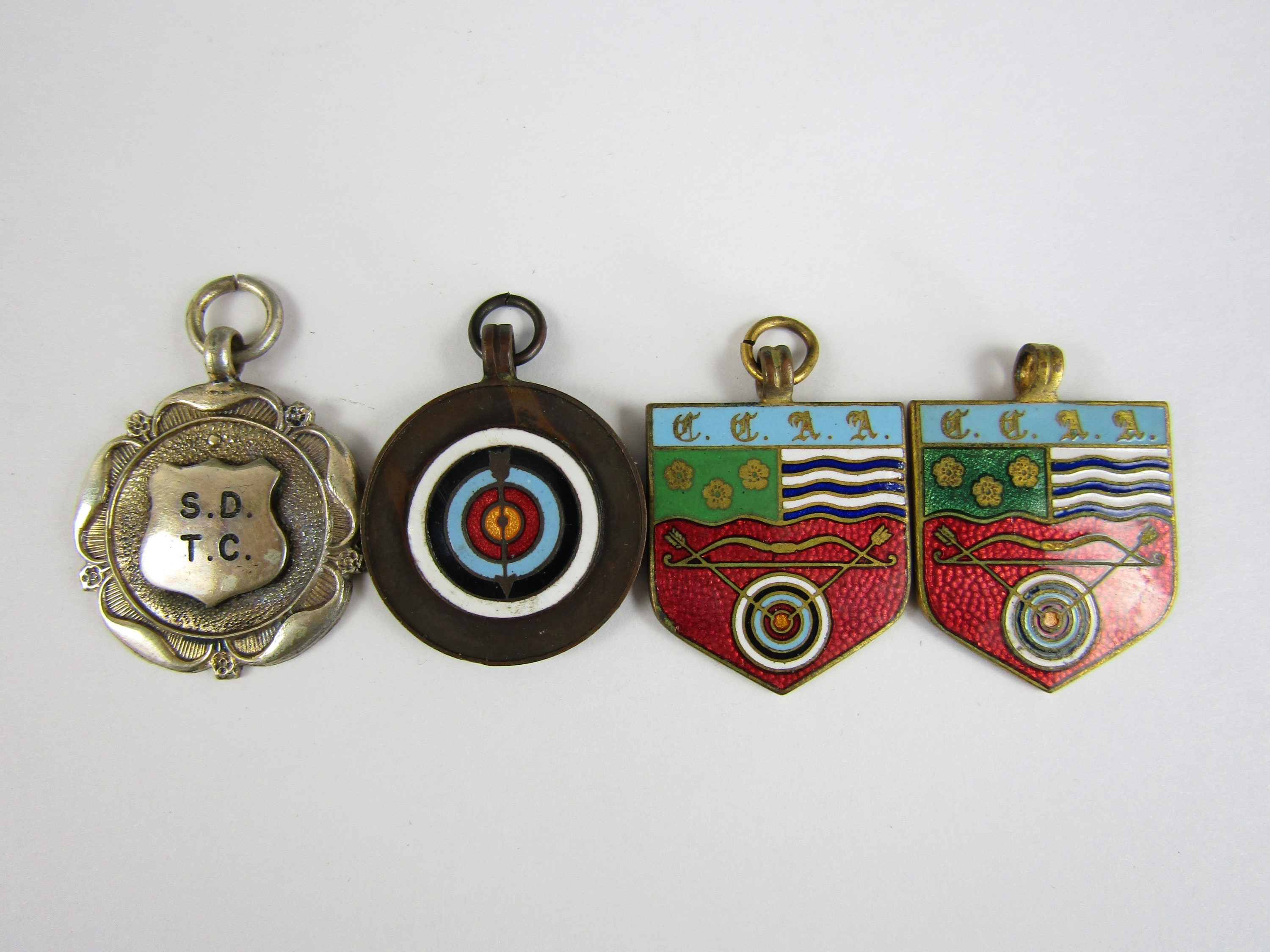 Lot 40 - Three vintage basse-taille enamelled archery medallions, together with one further electroplate