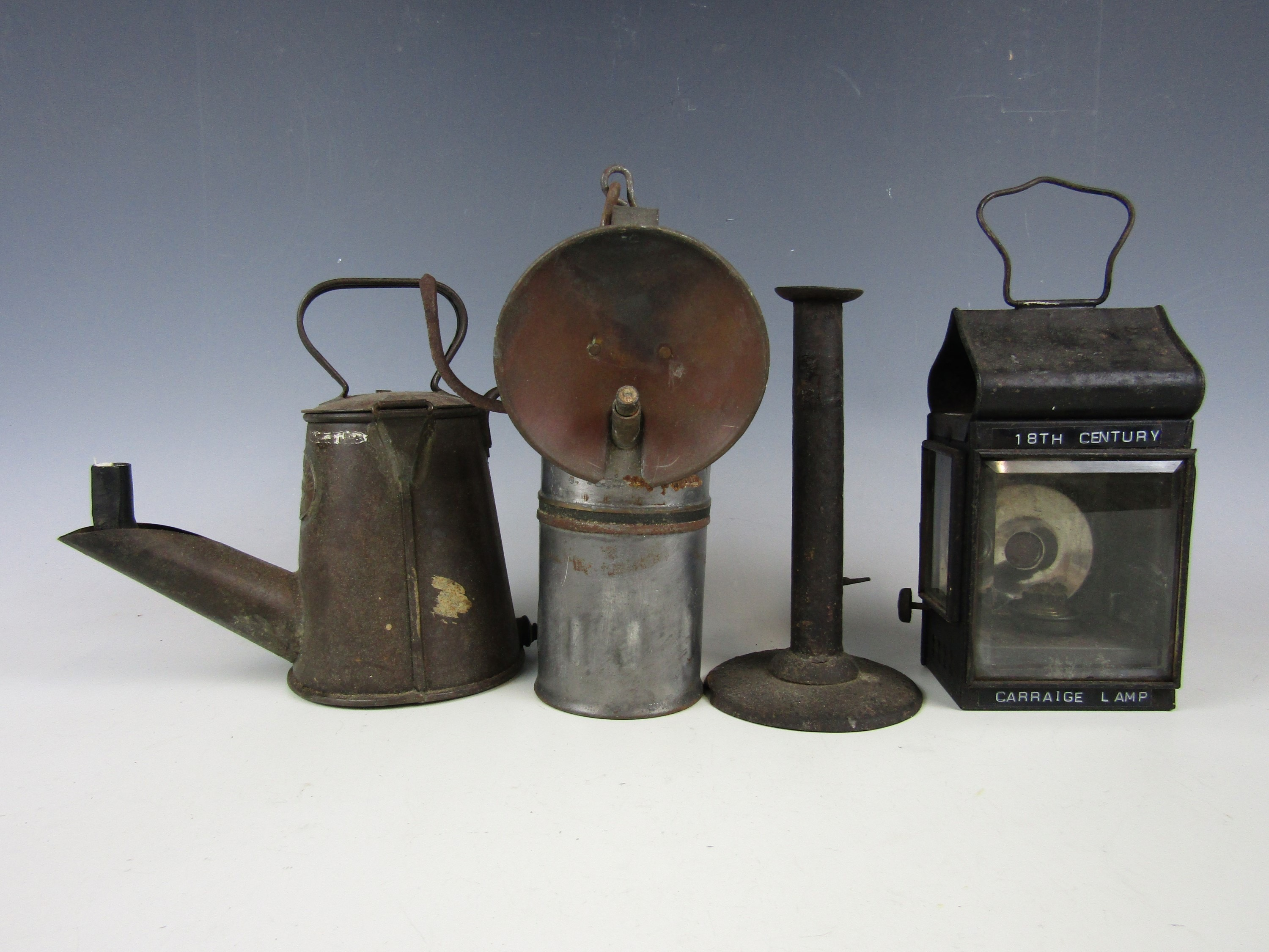 Lot 44 - A spout lamp by J Mills and Son of Millom, a steel elide-eject candlestick, a carriage lamp and a