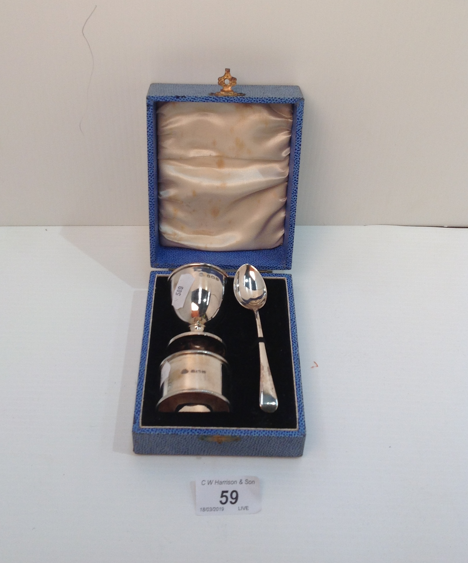Lot 59 - A silver three piece christening set comprising egg cup, spoon and napkin ring, Birmingham 1938,