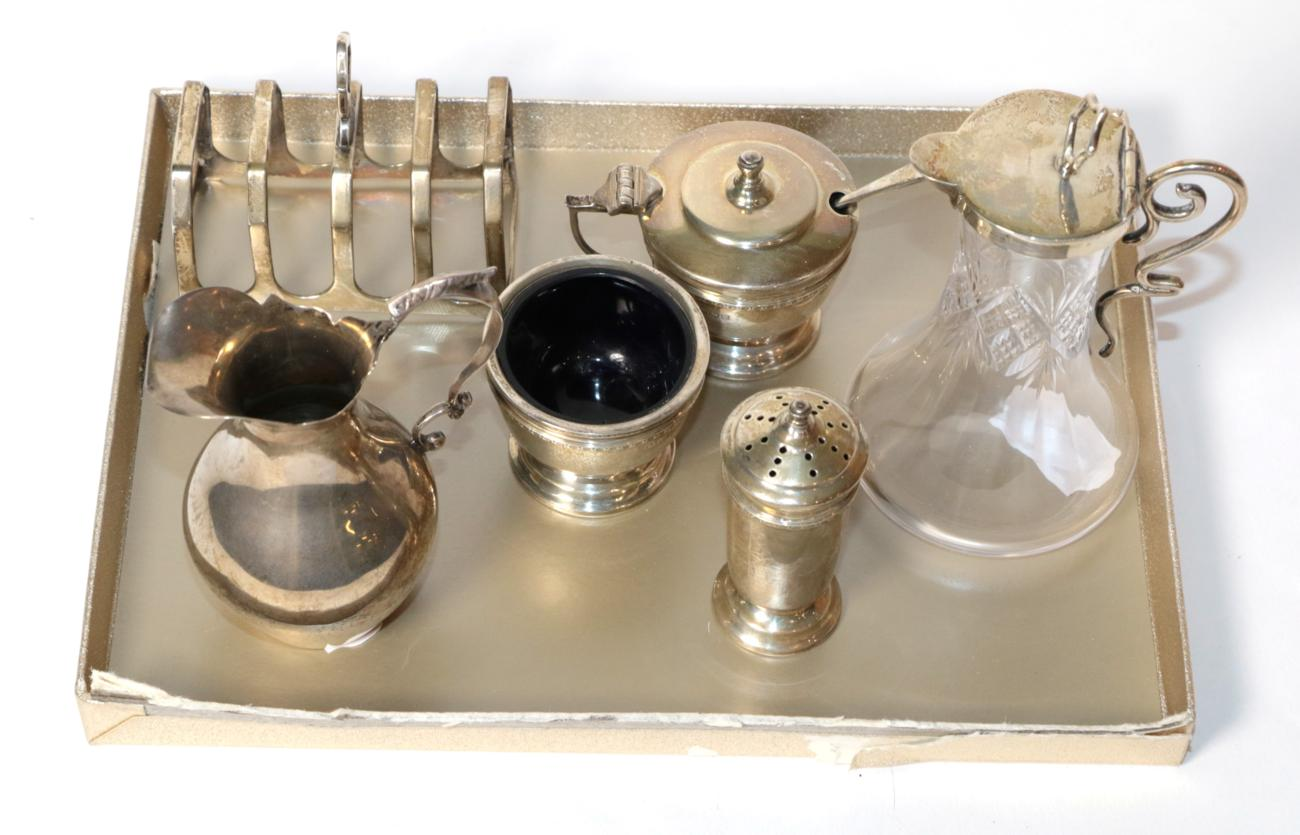 An unusual silver mounted whisky noggin, Birmingham 1903; a toast rack; a condiment set; and a cream