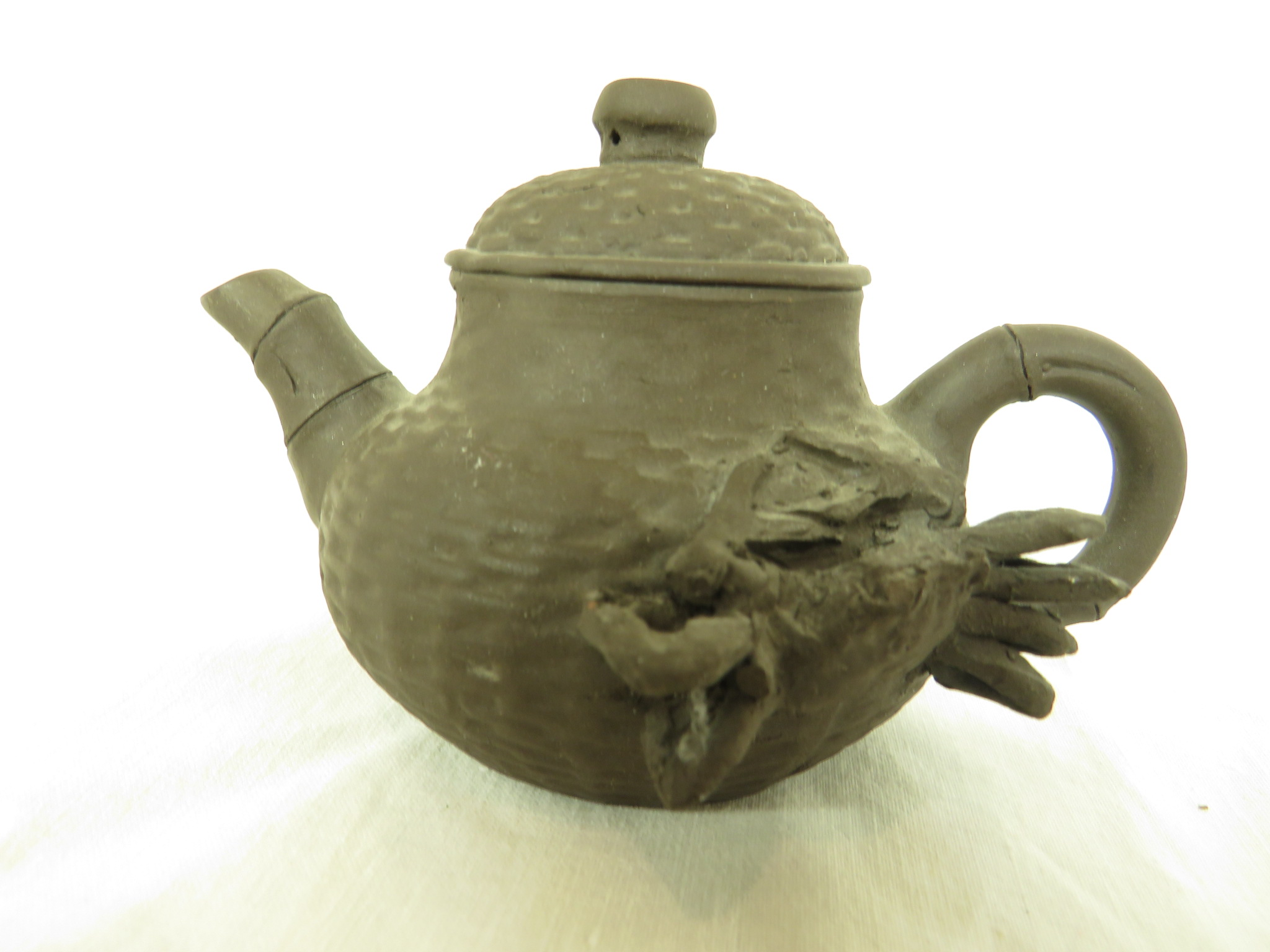 Lot 85 - Four Far Eastern ceramics - a Yixing type pottery teapot with impressed marks to base, within the