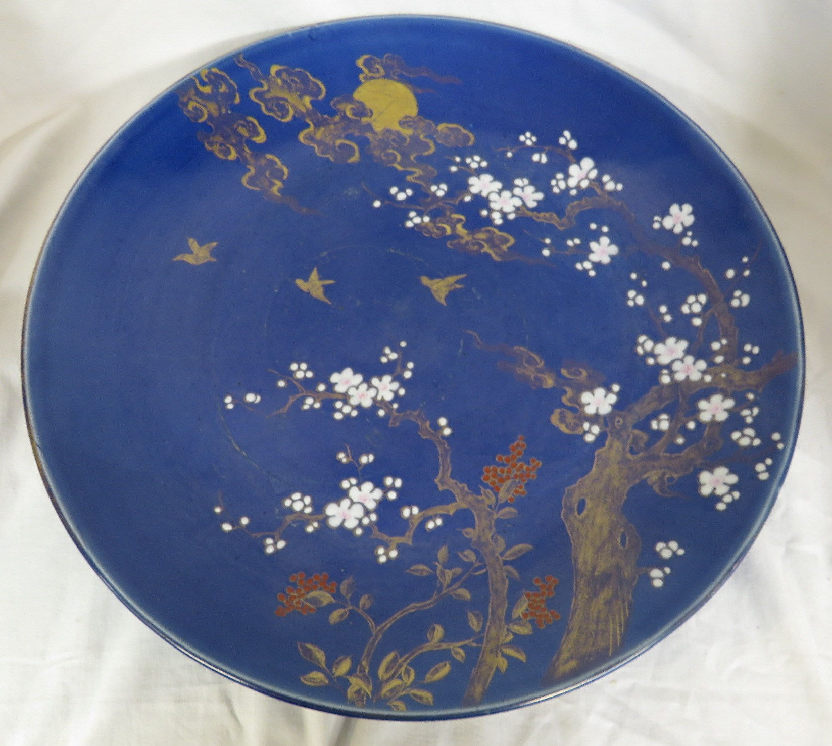 Lot 103 - Large blue ground porcelain dish decorated in enamels and gilding with moon and clouds over a