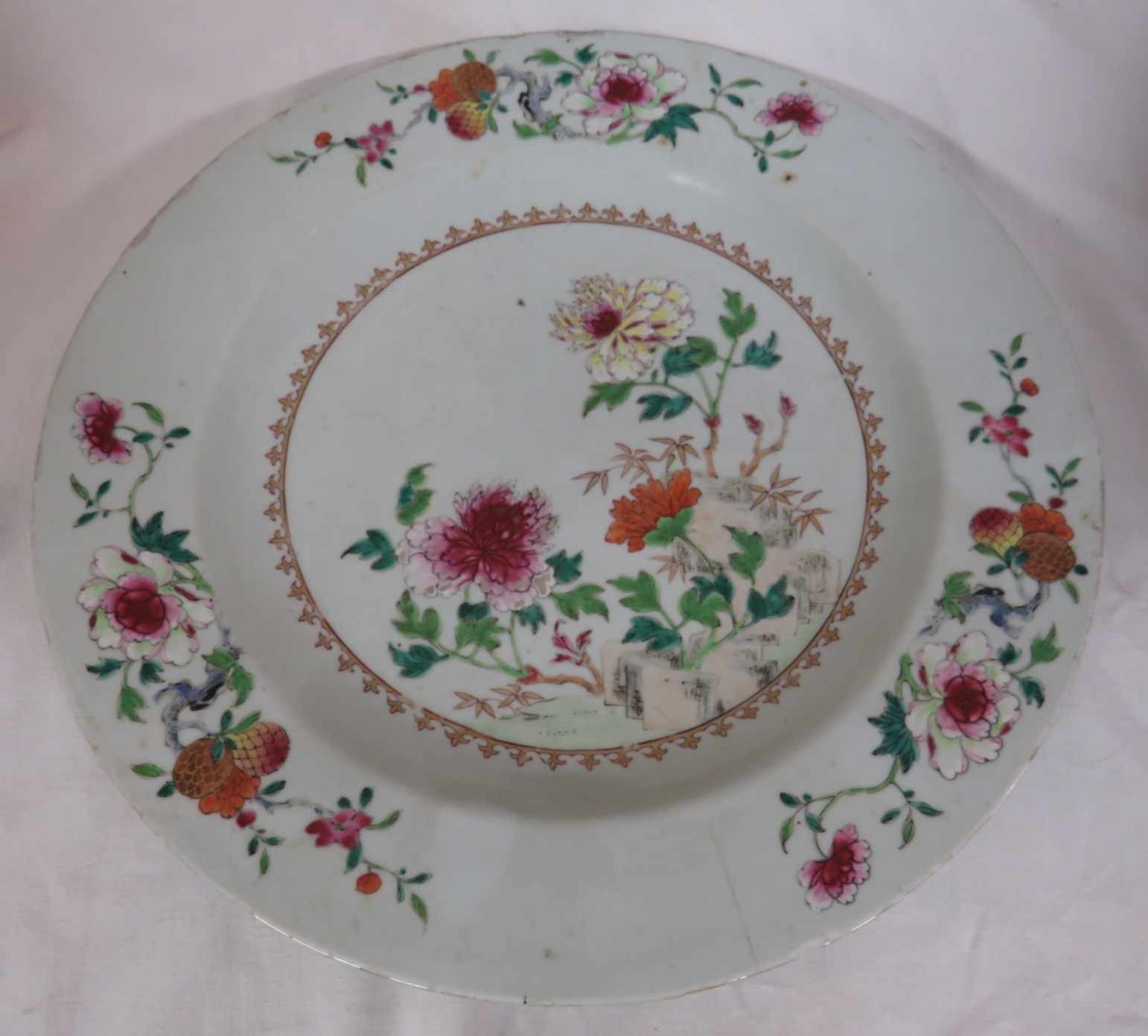 Lot 104 - A Chinese porcelain famille rose dish painted with flowering plants, the border with three
