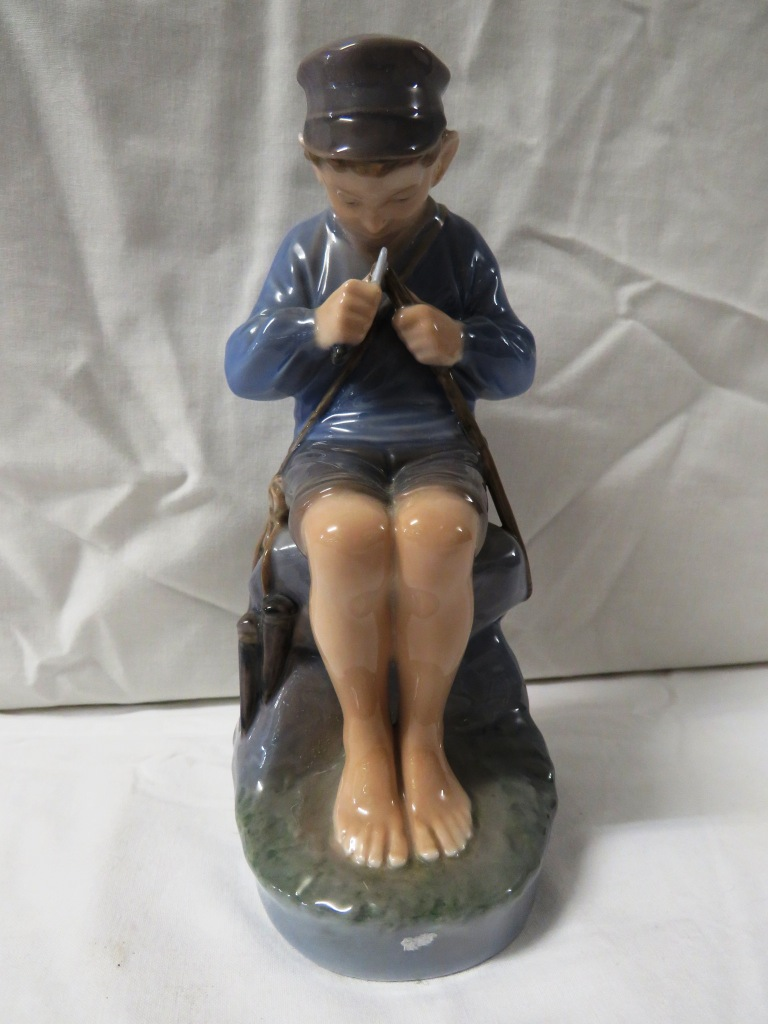 Lot 77 - Royal Copenhagen porcelain figure of a seated fishing boy whittling a stick, numbered 905, height