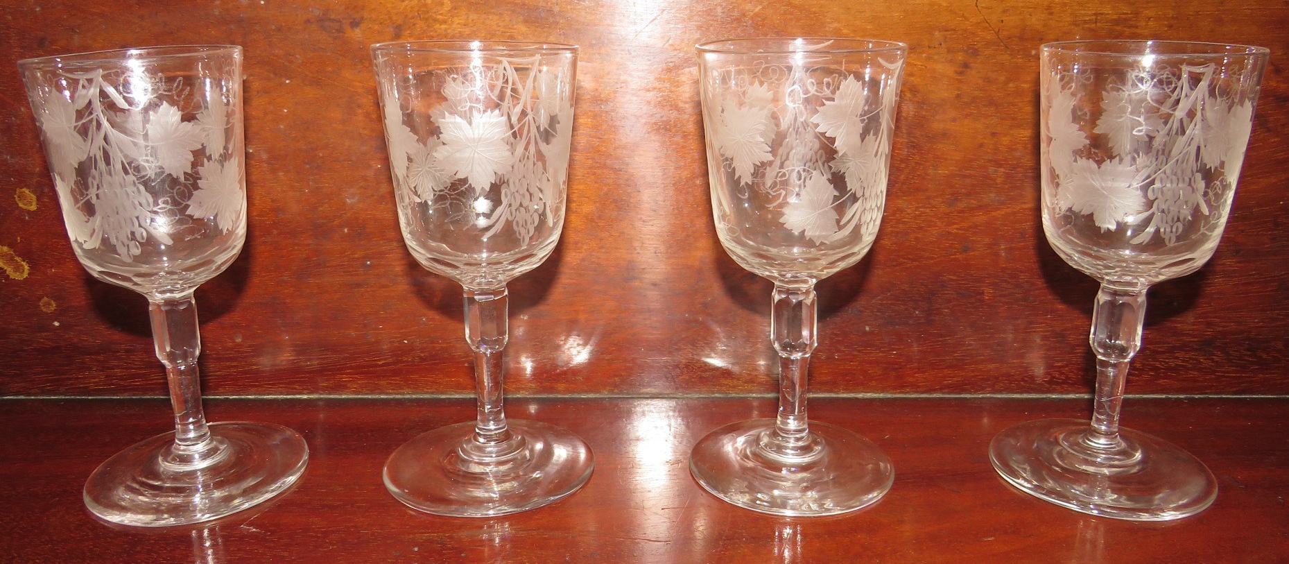 Lot 118 - Four 19th century wine glasses, the bowls etched with vines, the stems with octagonal knop, height