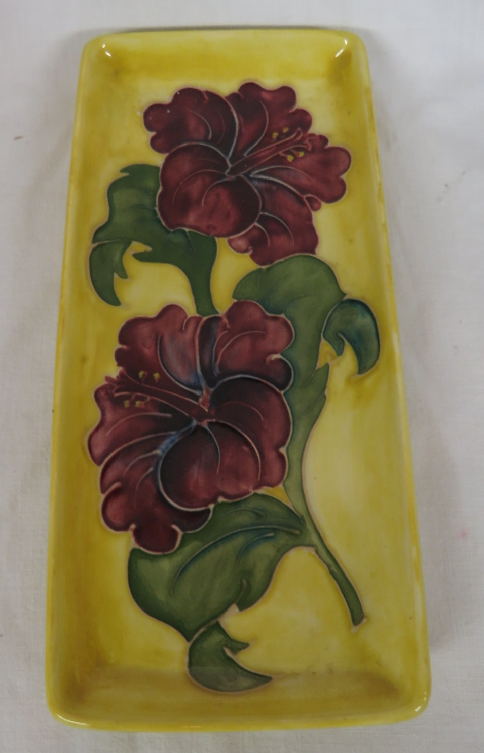 Lot 92 - Moorcroft pottery oblong dressing table dish, yellow ground with mauve flowers, 9cm x 20.5cm, the