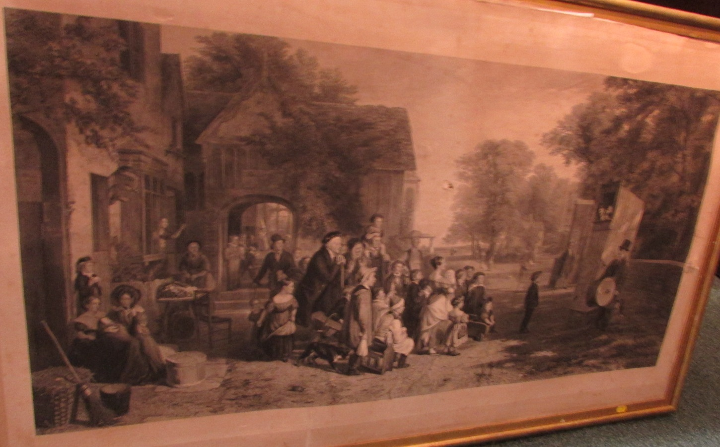 Lot 58 - 19th century engraving depicting a Punch and Judy show with a group of onlookers (65cm x 121cm) in a
